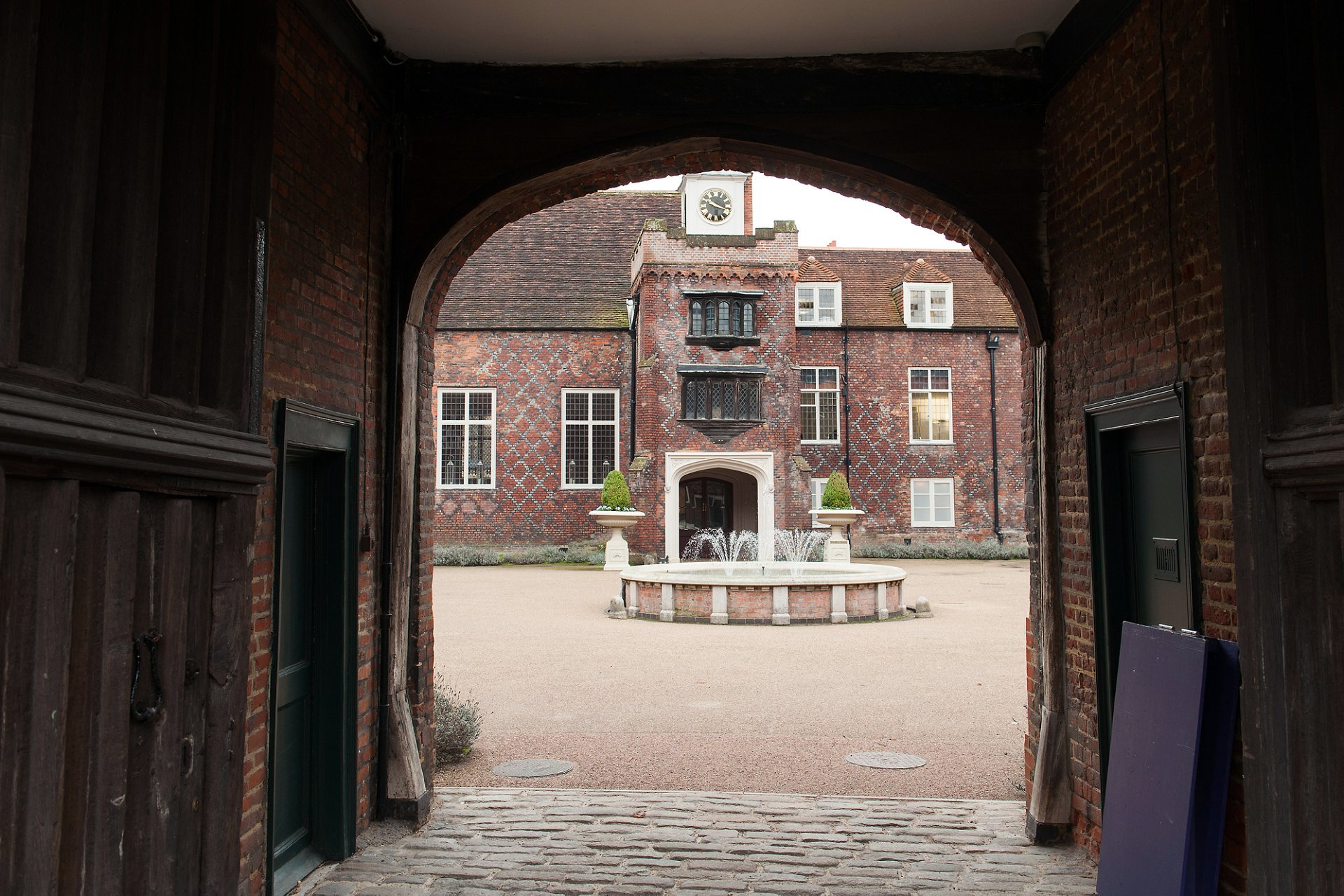 Historic Fulham Palace in west London looking through the wooden entrance gate and into the courtyard with the clock tower and fountain visible