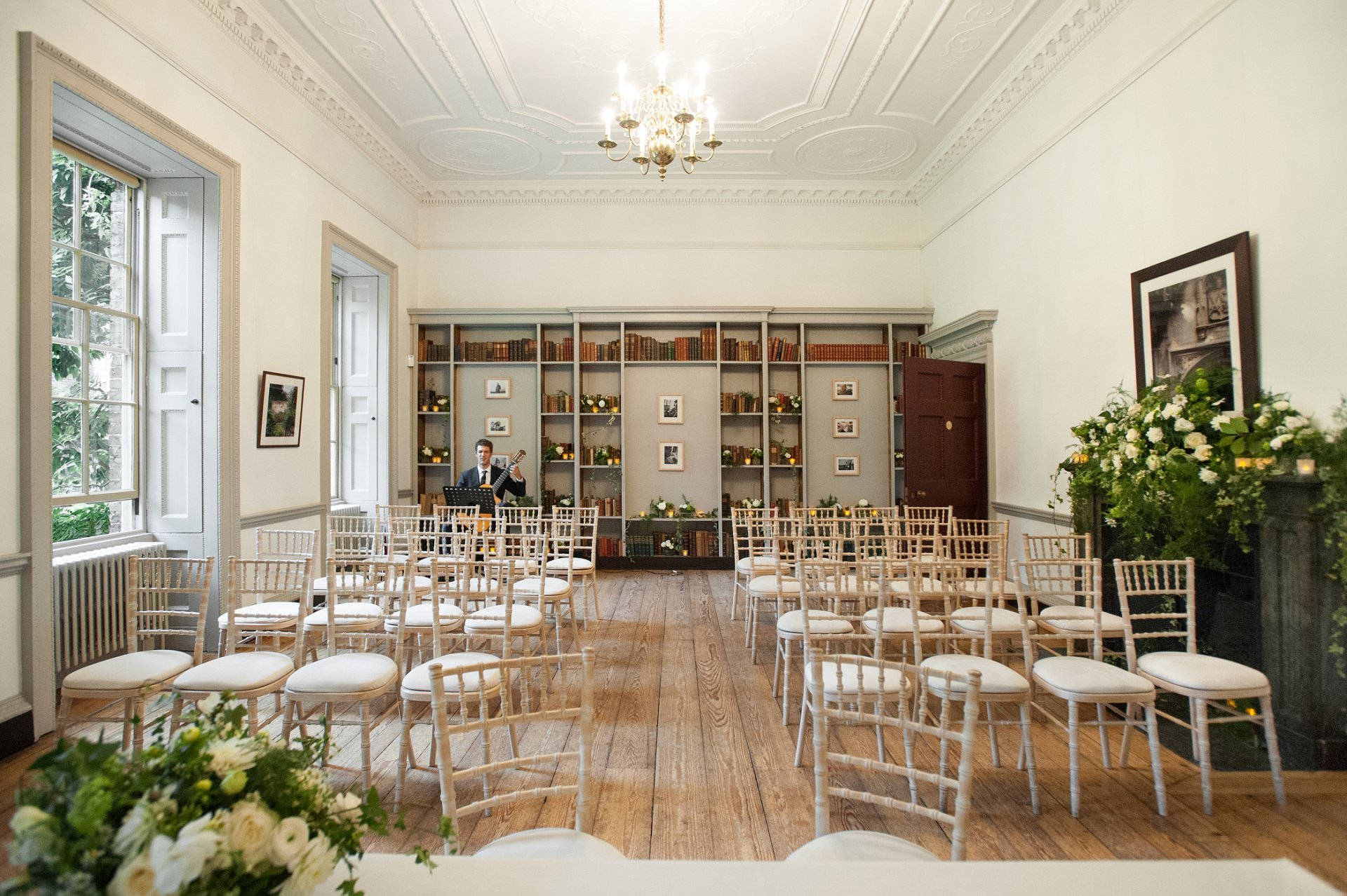 Fulham Palace's Bishop Terrick's Drawing Room with feature bookcase and marble fireplace all decorated with flowers in creams and greens along with tealights. This is how the room looks laif out for a civil wedding ceremony for 30 guests