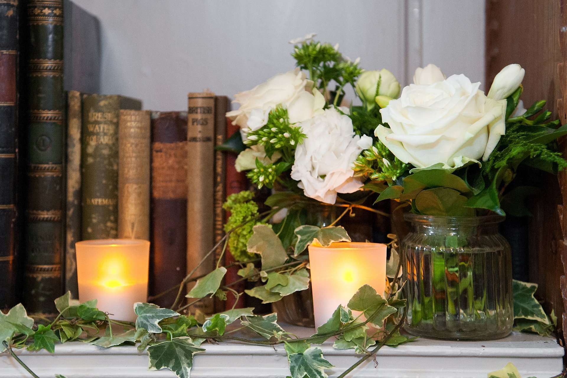 The bookcase in the Bishop Terrick's Drawing Room is an ideal space to fit floral arrangements, in this case pretty creams, whites and greens including trailing ivy in mis-matches glass vases and jam jars along with electric tealights