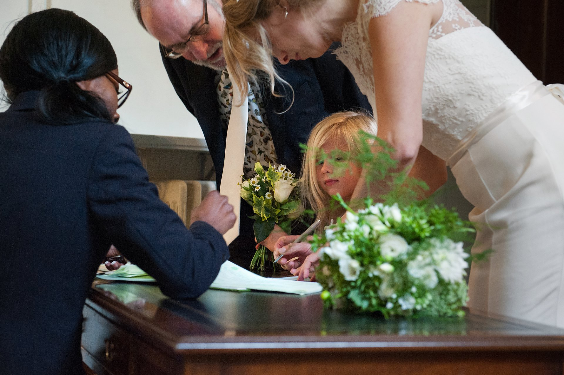 The brides' father and daughter watch as the bride completes the marriage certificate ahead of her Fulham Palace wedding