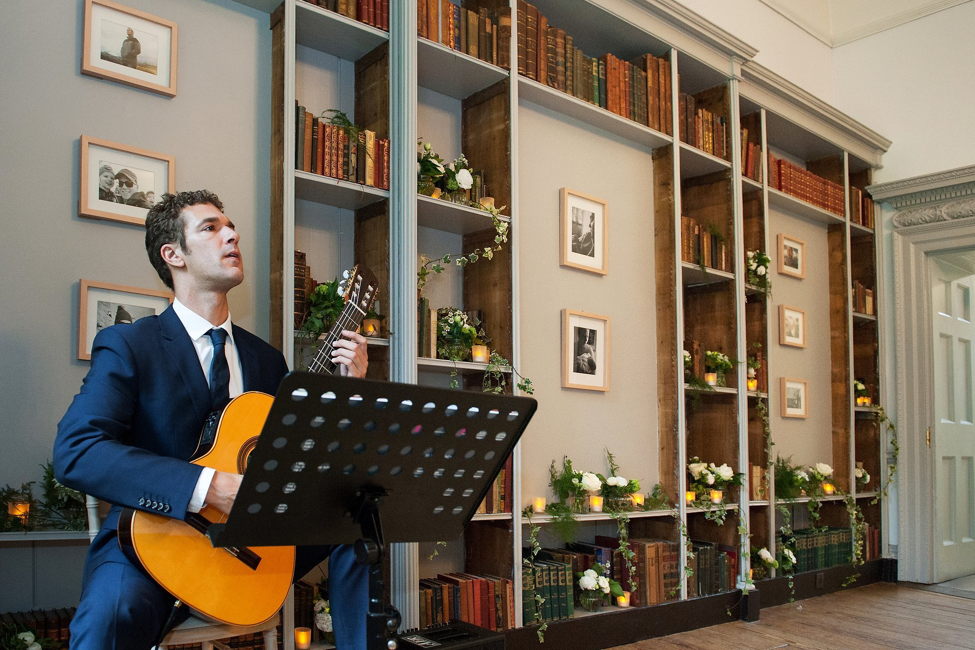 Fulham Palace Wedding Photography - guitarist Peter Black plays a classical piece for the bride's entrance into the Bishop Terrick's Drawing Room at Fulham Palace with the bookcase behind him decorated with flowers and candles