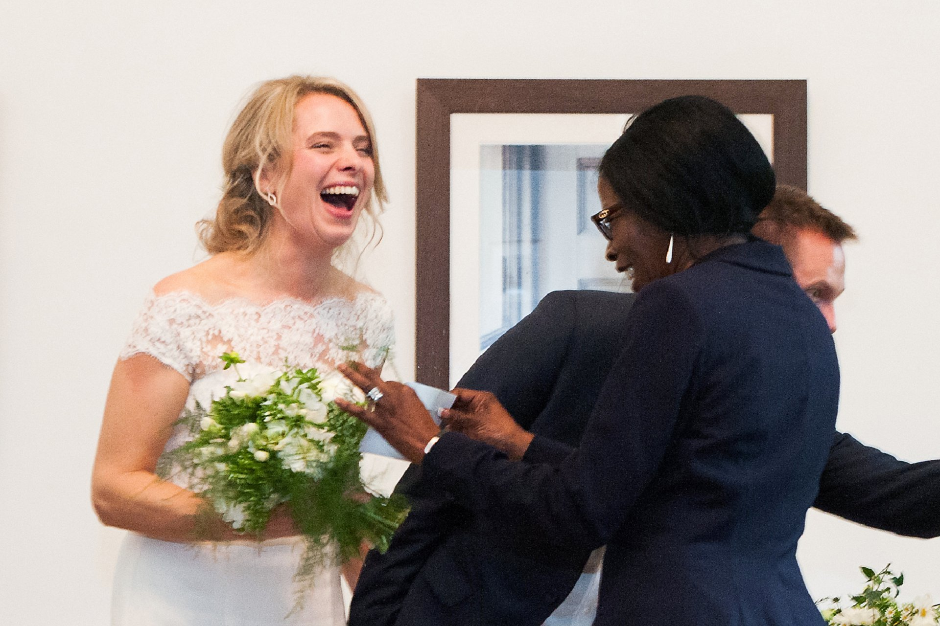 The Hammersmith & Fulham Registry Office registrar makes teh bride laugh as she hands her the marriage certificate