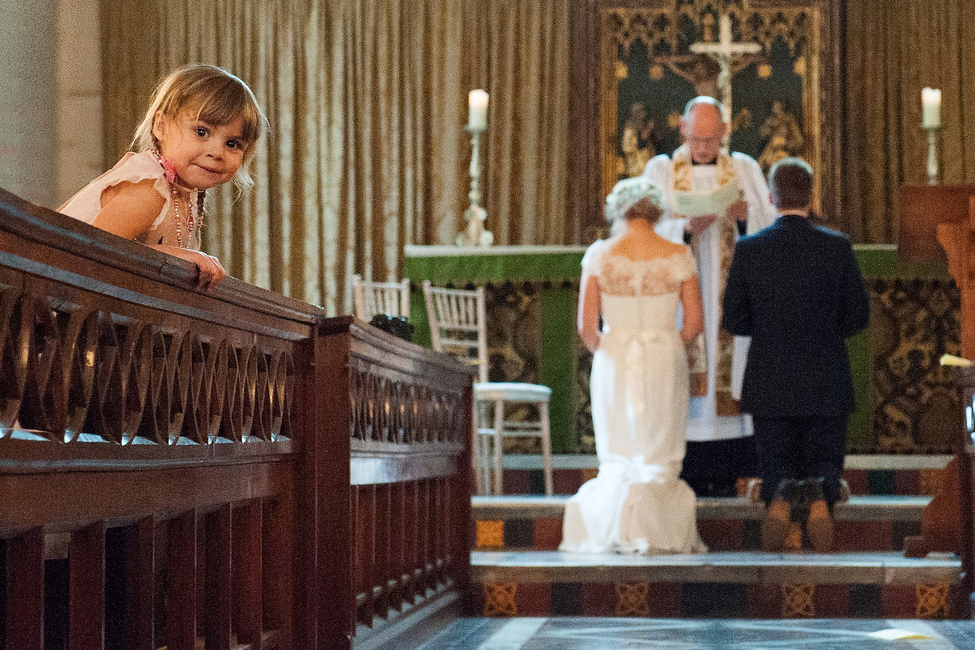 While the bride and groom receive a blessing in Fulham Palce's Tait Chapel a little girl looks back over the pew - so adorable!