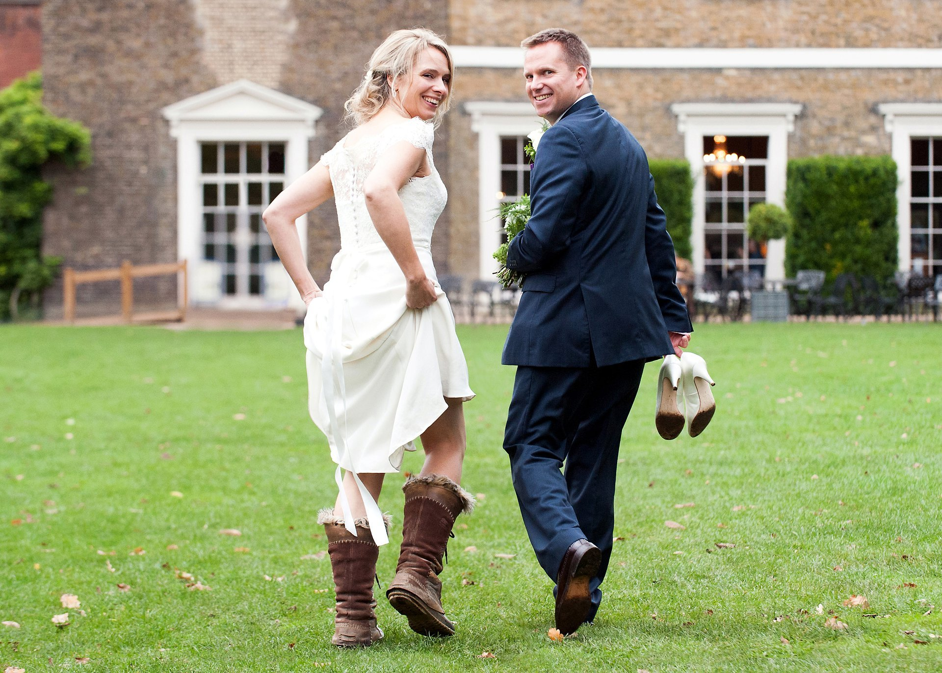 Fulham Palace Wedding Photography - the happy couple walking across the lawn at Fulham Palace, the bride wearing the photographer's very old and scruffy sorel boots