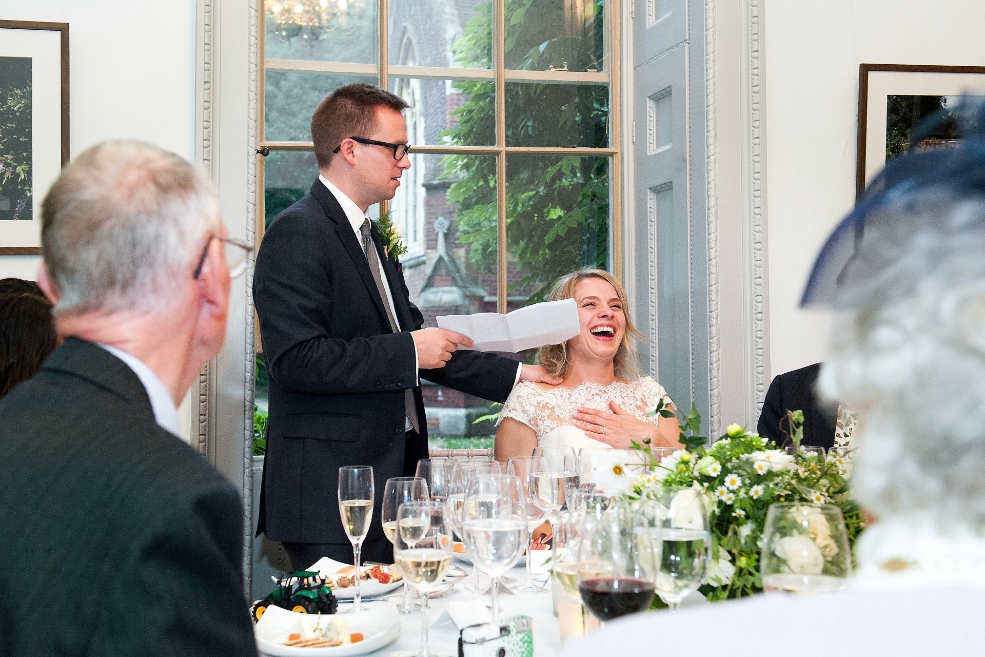 Bride laughing as her husband makes as joke during his speech