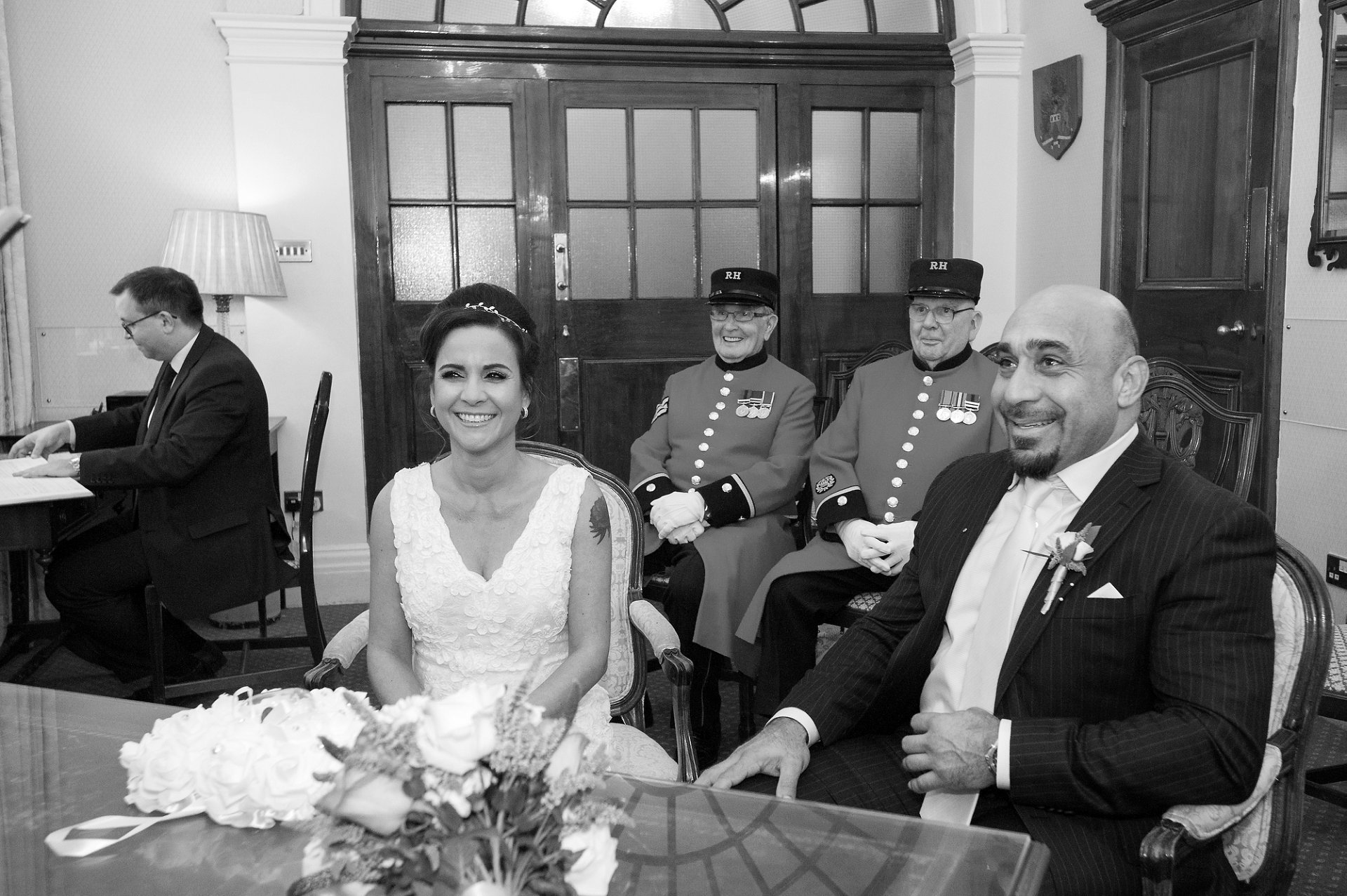 Bride & groom smiling during their wedding ceremony in the Rossetti Room at Chelsea Old Town Hall with Chelsea Pensioners looking on