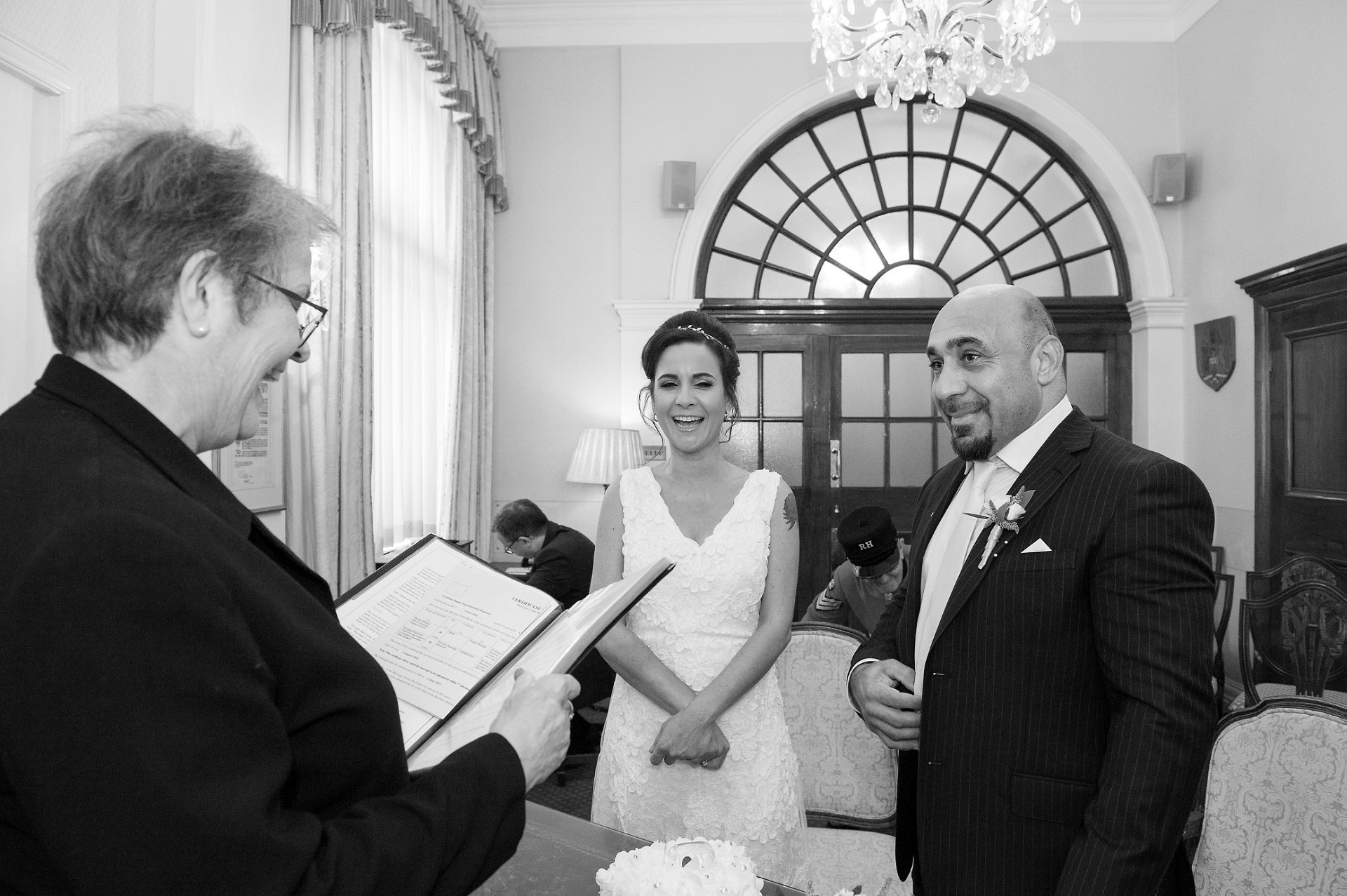 Kensington & Chelsea Registrar smiling at bride and groom during their wedding ceremony in Chelsea Old Town Hall