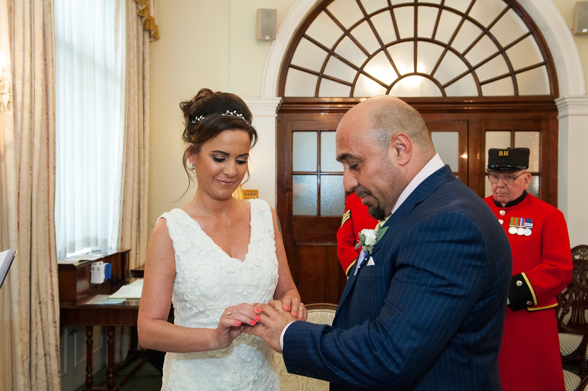 Bride places ring on groom's finger during wedding ceremony at Chelsea Registry Office