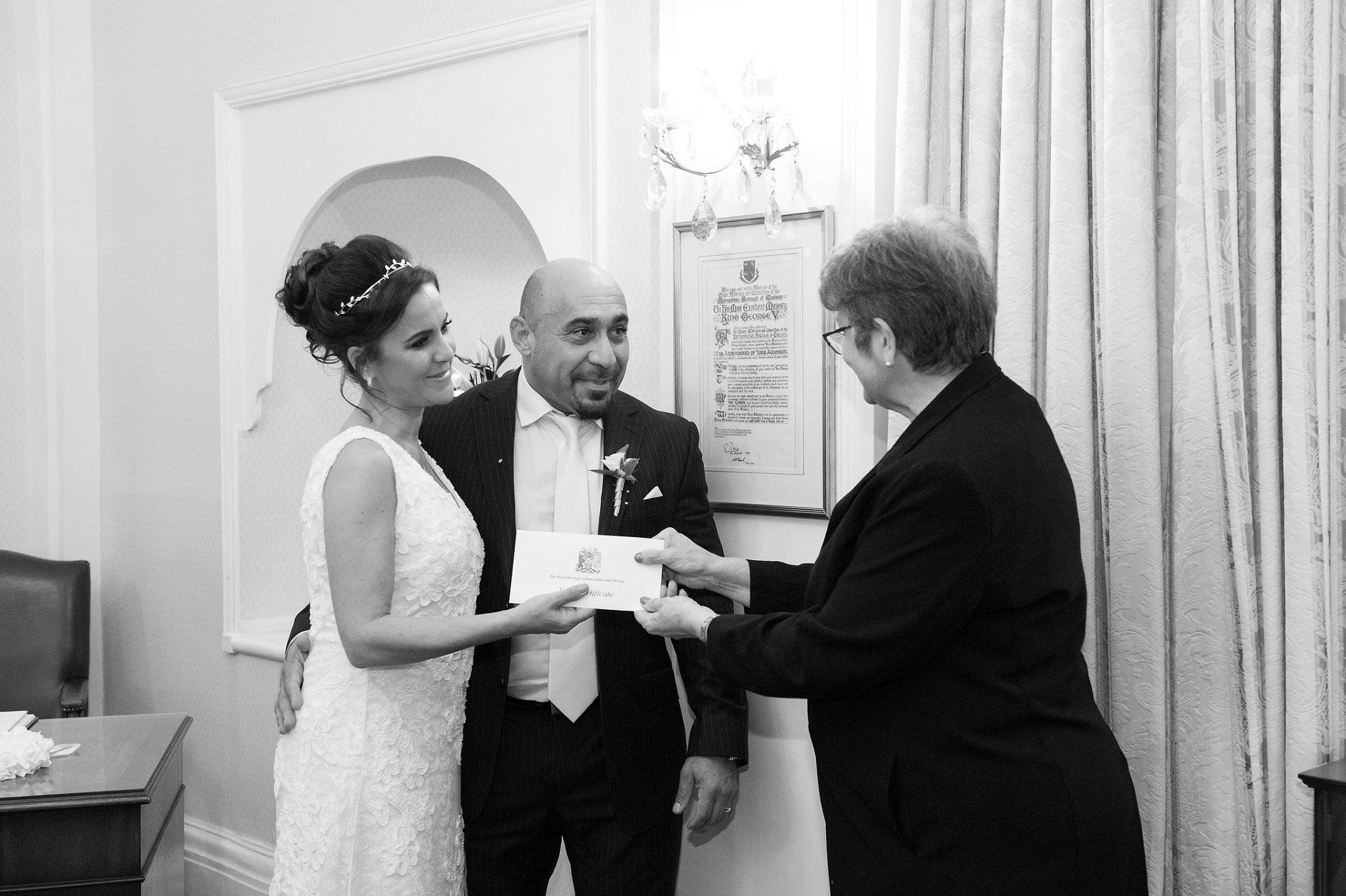Chelsea Registrar hands Wedding Certificate to bride & groom