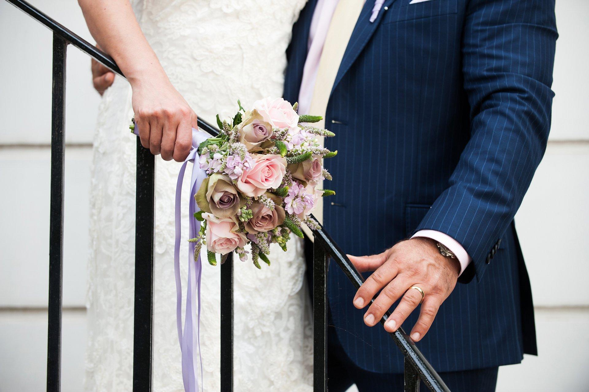 Close up of wedding bouquet of vintage tea and pale pink roses and wedding band