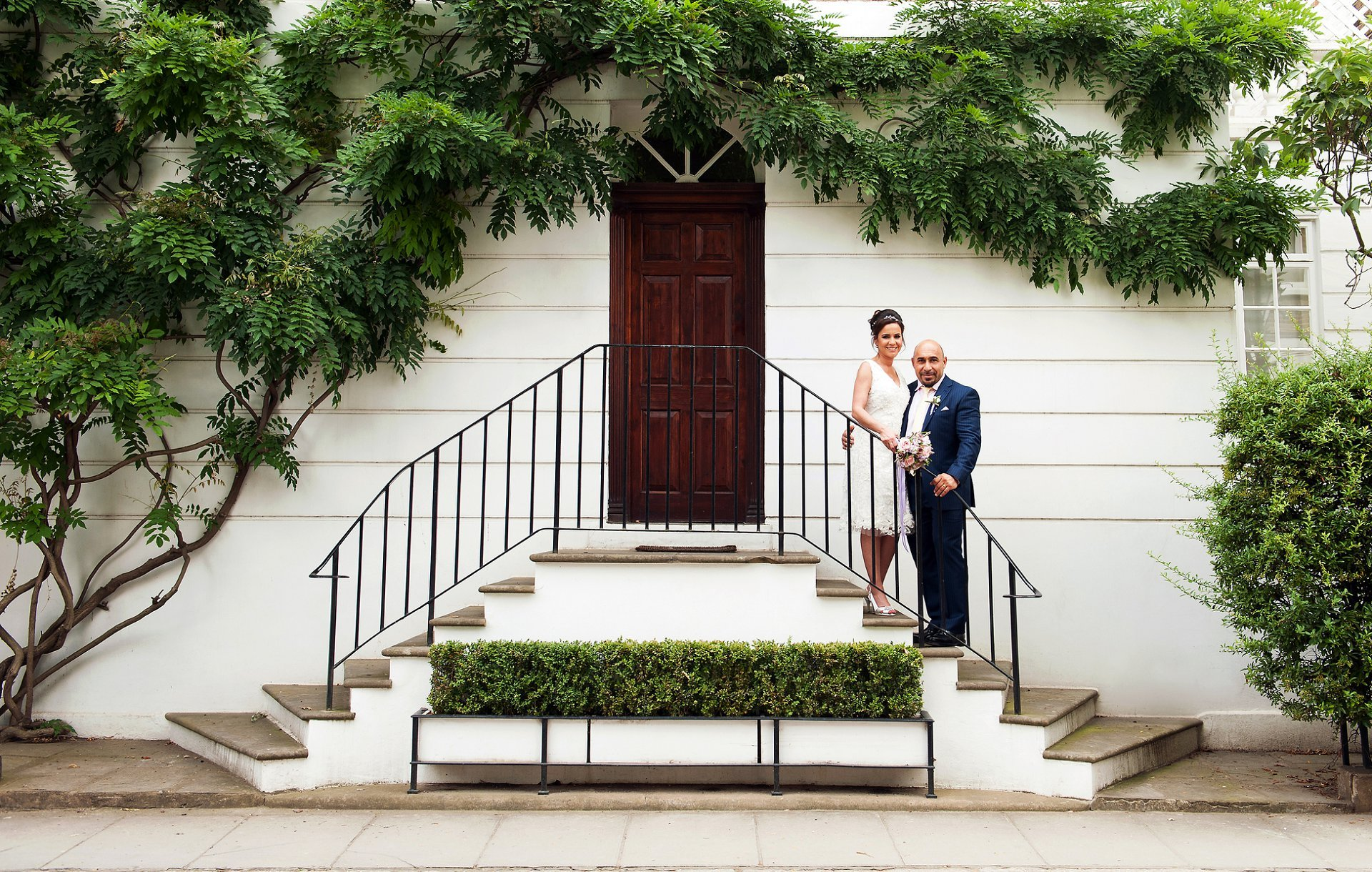 Wisteria branches and leaves and a pretty Chelsea building make an ideal backdrop for wedding photos
