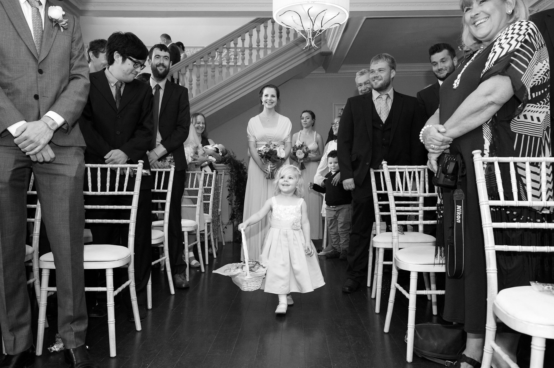 Adorable flower girl walks down the aisle in the Willow Room at Morden Hall