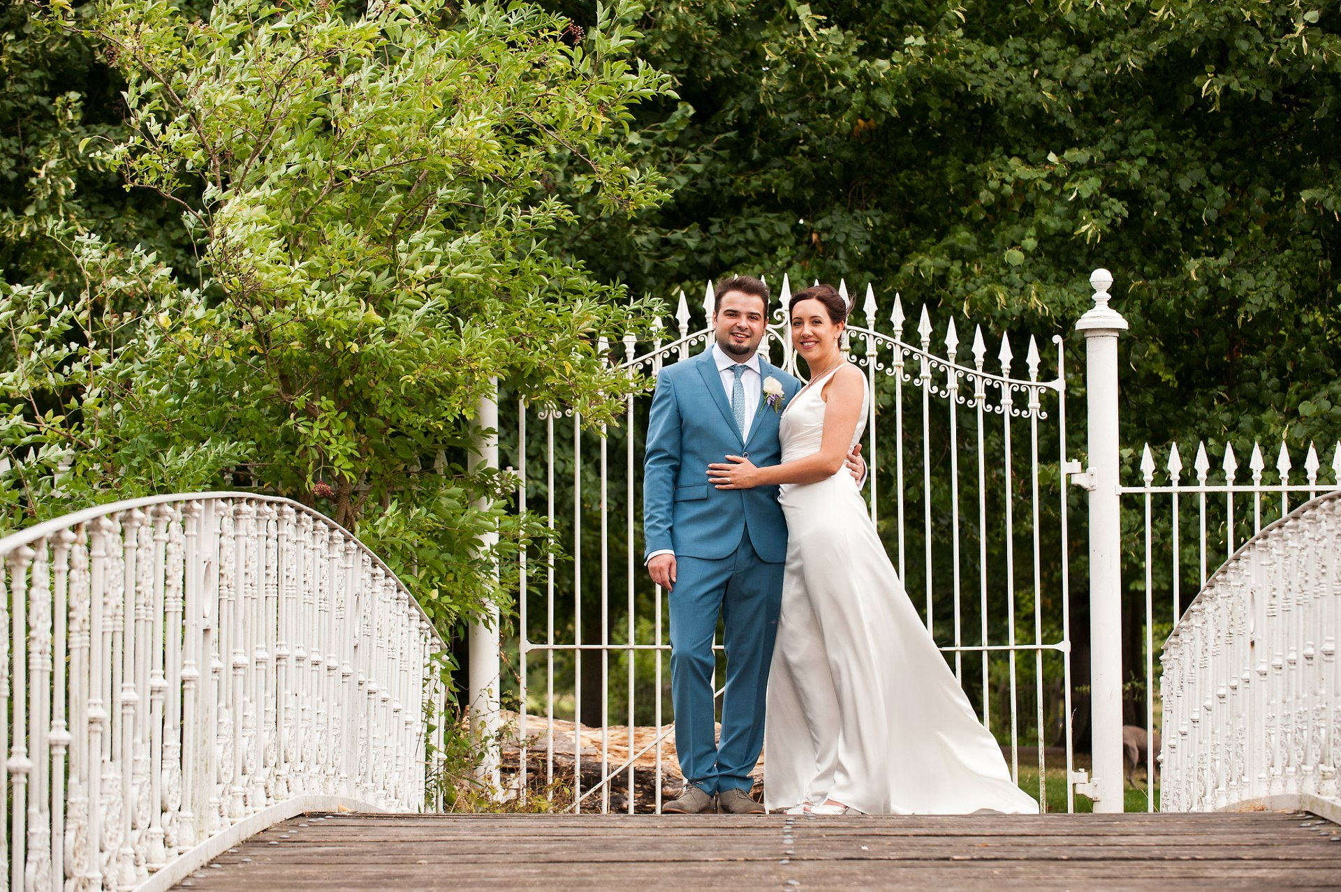Stylish bride & groom on the little white bridge at Morden Hall in south London