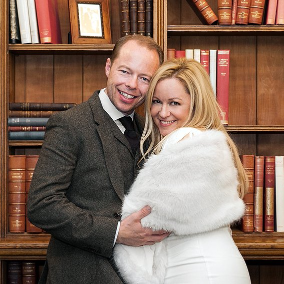 Mayfair Library wedding photographer Emma Duggan here a couple pose in front of the library bookcase after their Westminster Register Office civil wedding ceremony held in the Marylebone Room