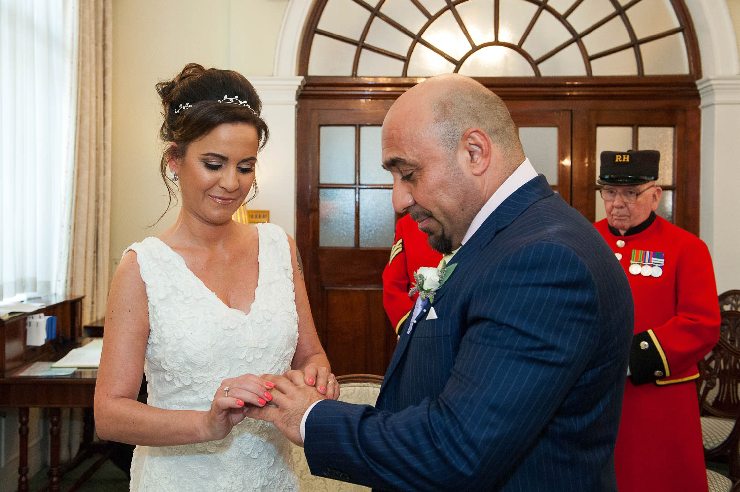 The exchange of rings during a civil wedding ceremony at Chelsea Register Office's Rossetti Room.