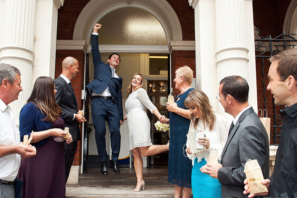 Register office wedding photographer Emma Duggan for weddings at at Chelsea Register Office, Mayfair Library, Greenwich Register Office, and Woolwich Old Town Hall. Here, a couple leaping into the air after their Mayfair Library wedding