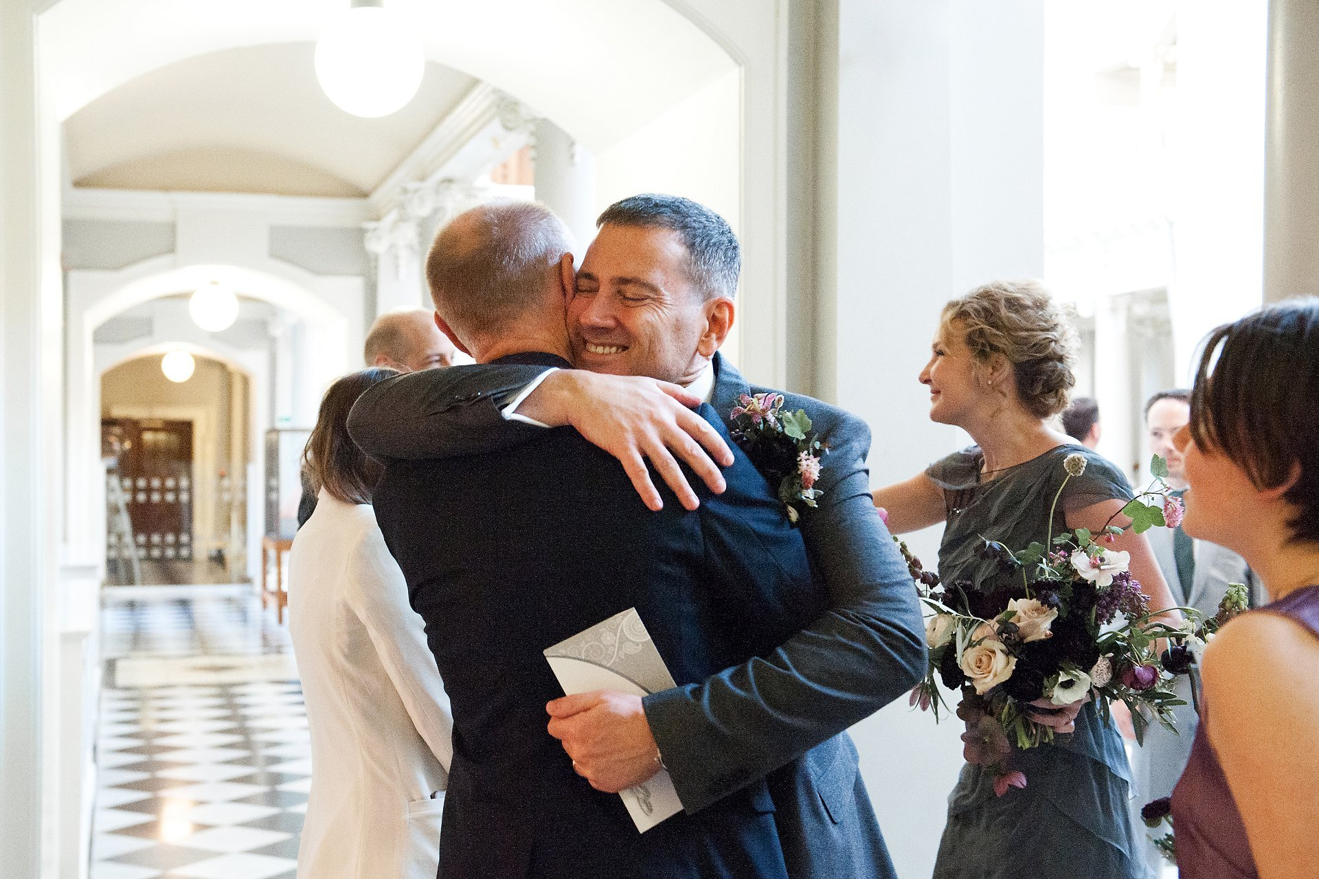 Groom hugs his friend after getting married at Woolwich Town Hall
