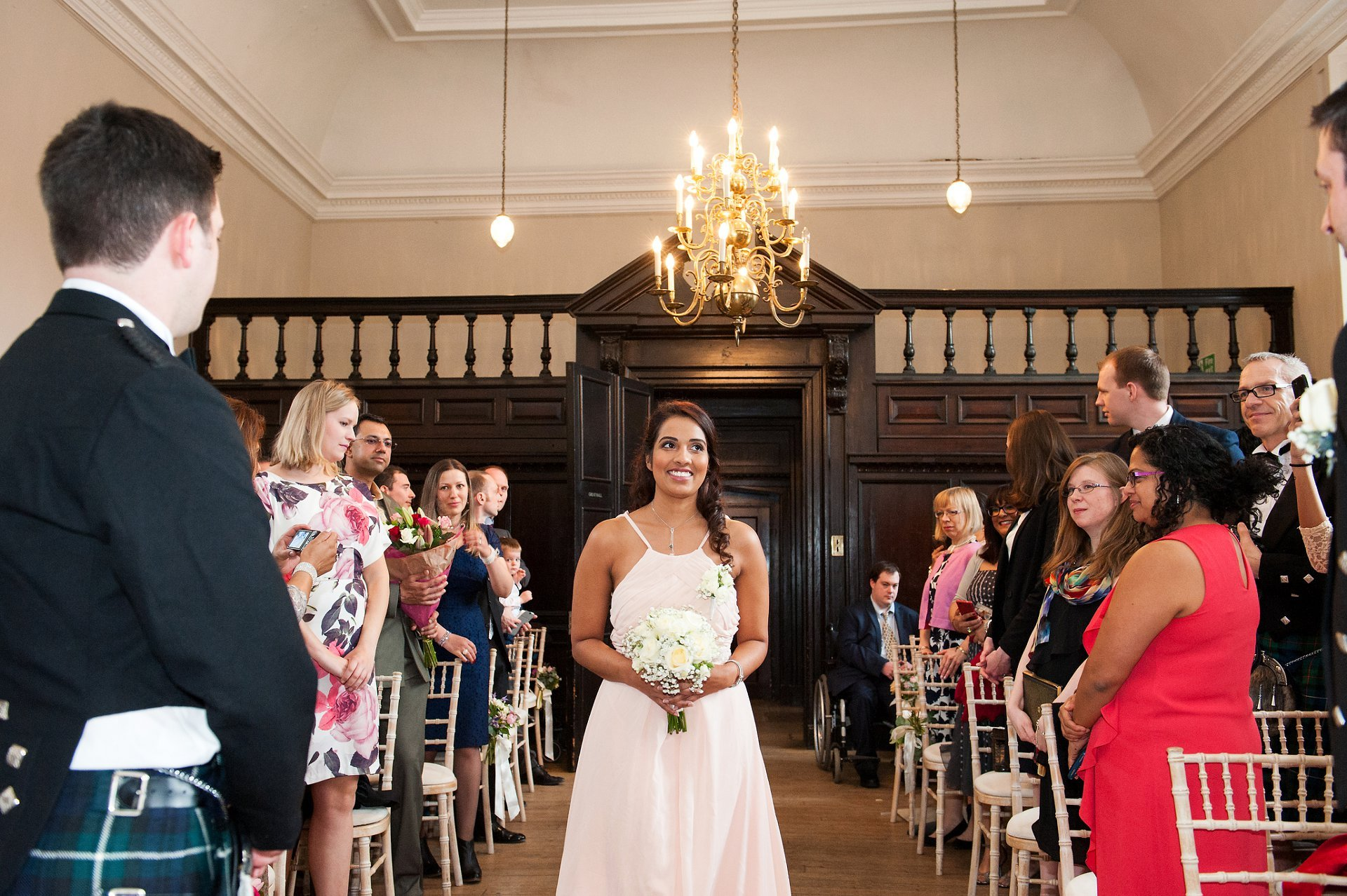 Bridesmaid Natasha enters the Great Hall in Fulham Palace just before her sister and parents