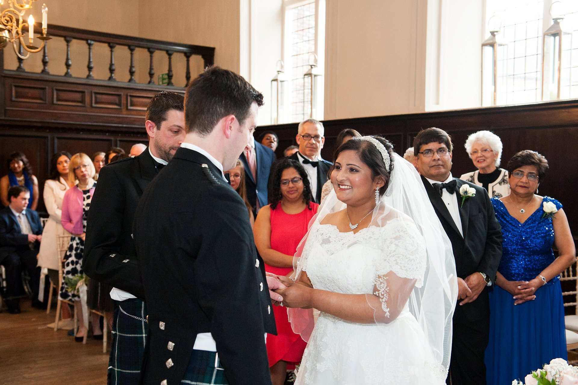 Feriel exchanges rings with Adam during their Fulham Palace Great Hall wedding