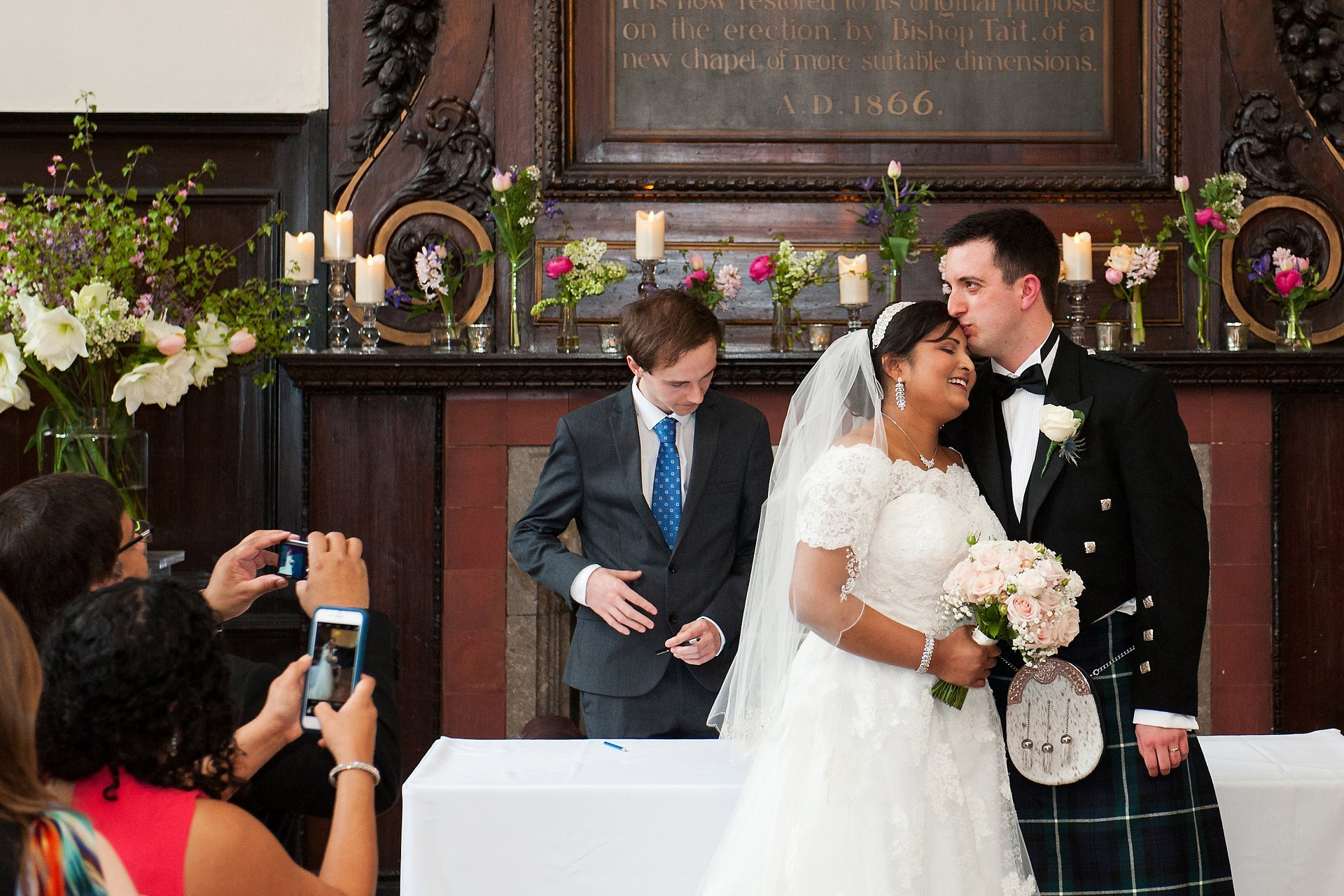Groom kisses his bride after their Fulham Palace Great Hall wedding