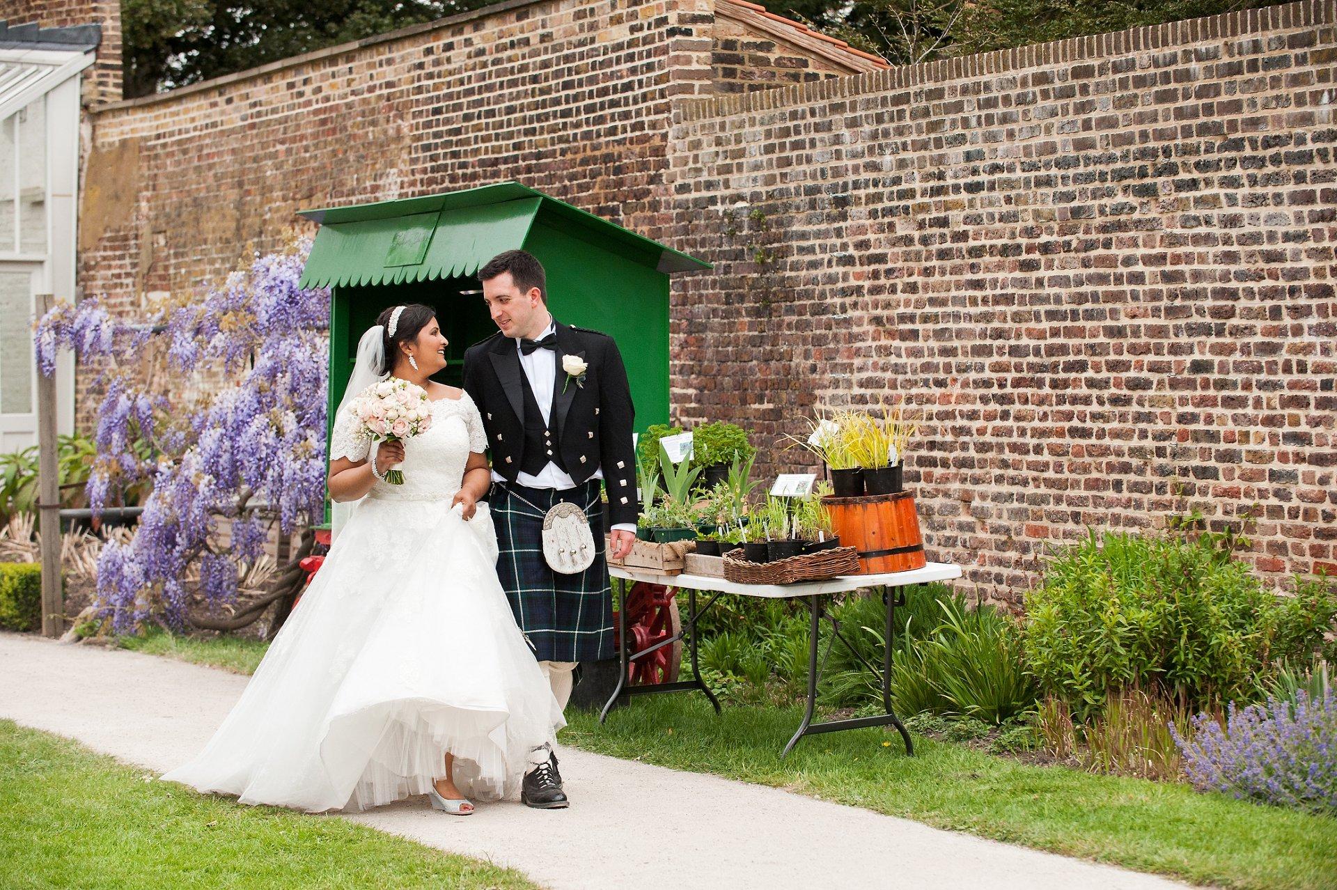 Bride & Groom walk through Fulham Palace's botanical garden
