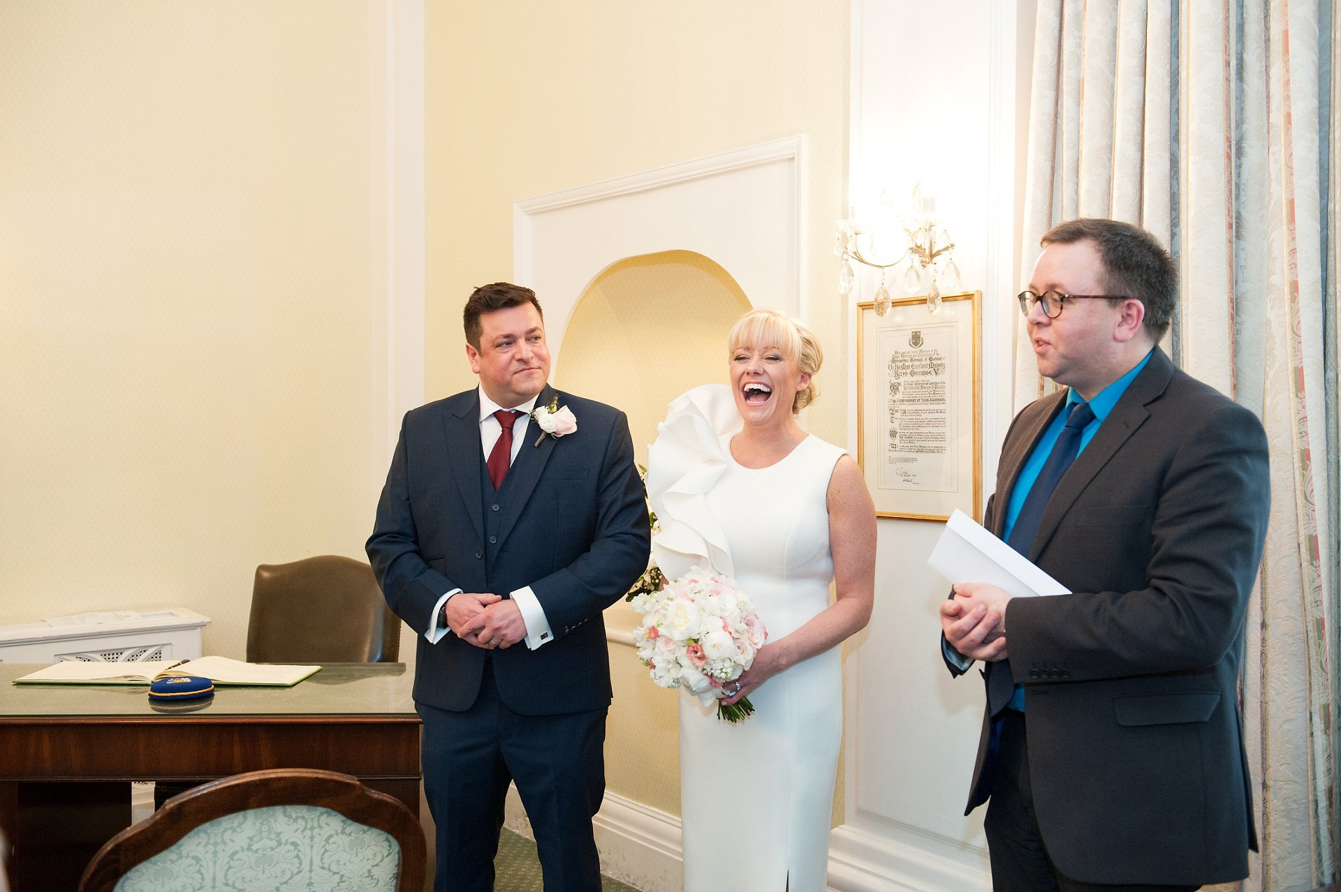 Bride & Groom laughing as Kensington & Chelsea Registrar Damian hands over their marriage license