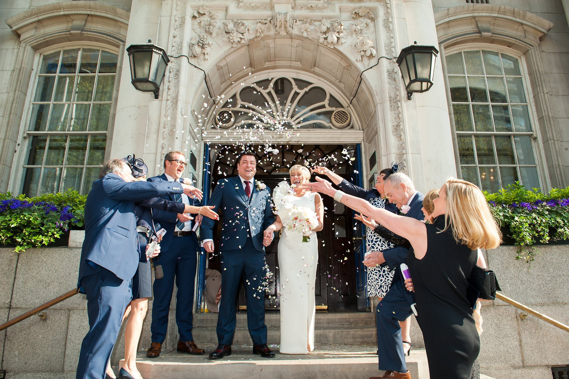 Bride & groom on the famous Chelsea Old Town Hall steps with guests throwing confetti