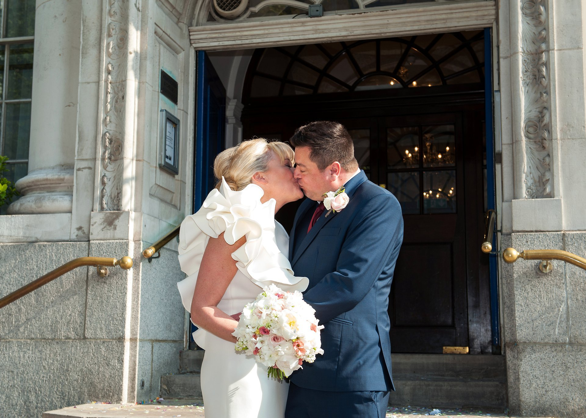 Bride & groom kissing on the steps of Chelsea Register Office