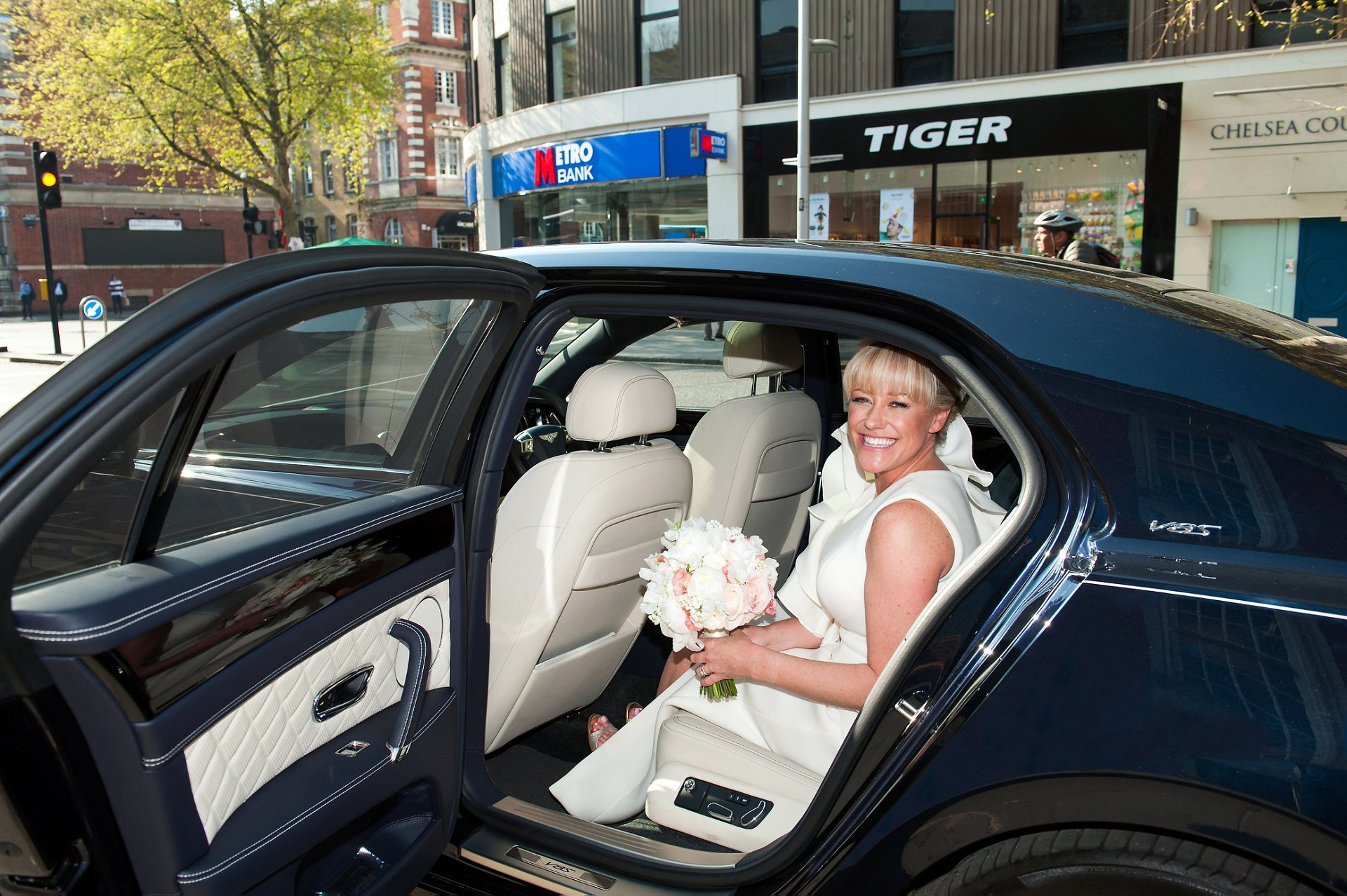 Bride gets into Bentley on the King's Road after her wedding ceremony in Chelsea Old Town Hall