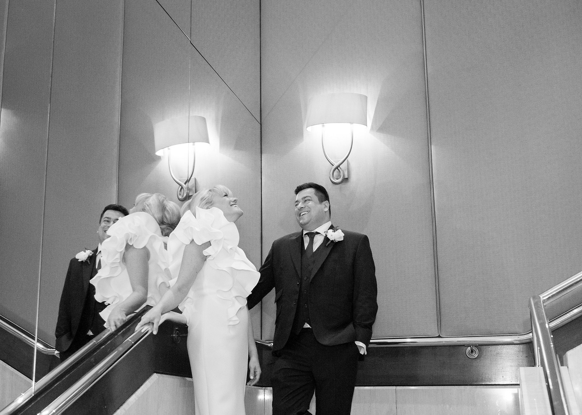 Bride and groom laughing on the staircae at Jumeirah Carlton