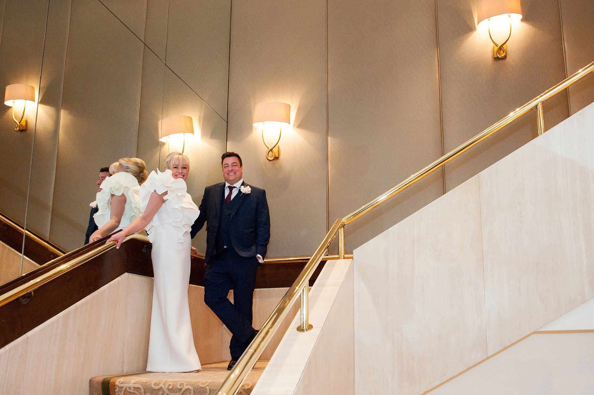 Bride & groom on the staircase at the Jumeirah Carlton
