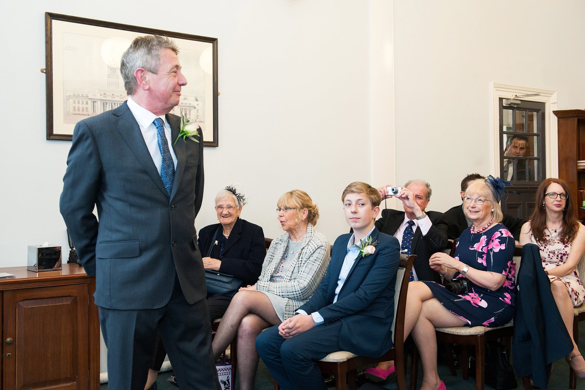Groom, Sid, watches his bride enter the Marylebone Room at Mayfair Library