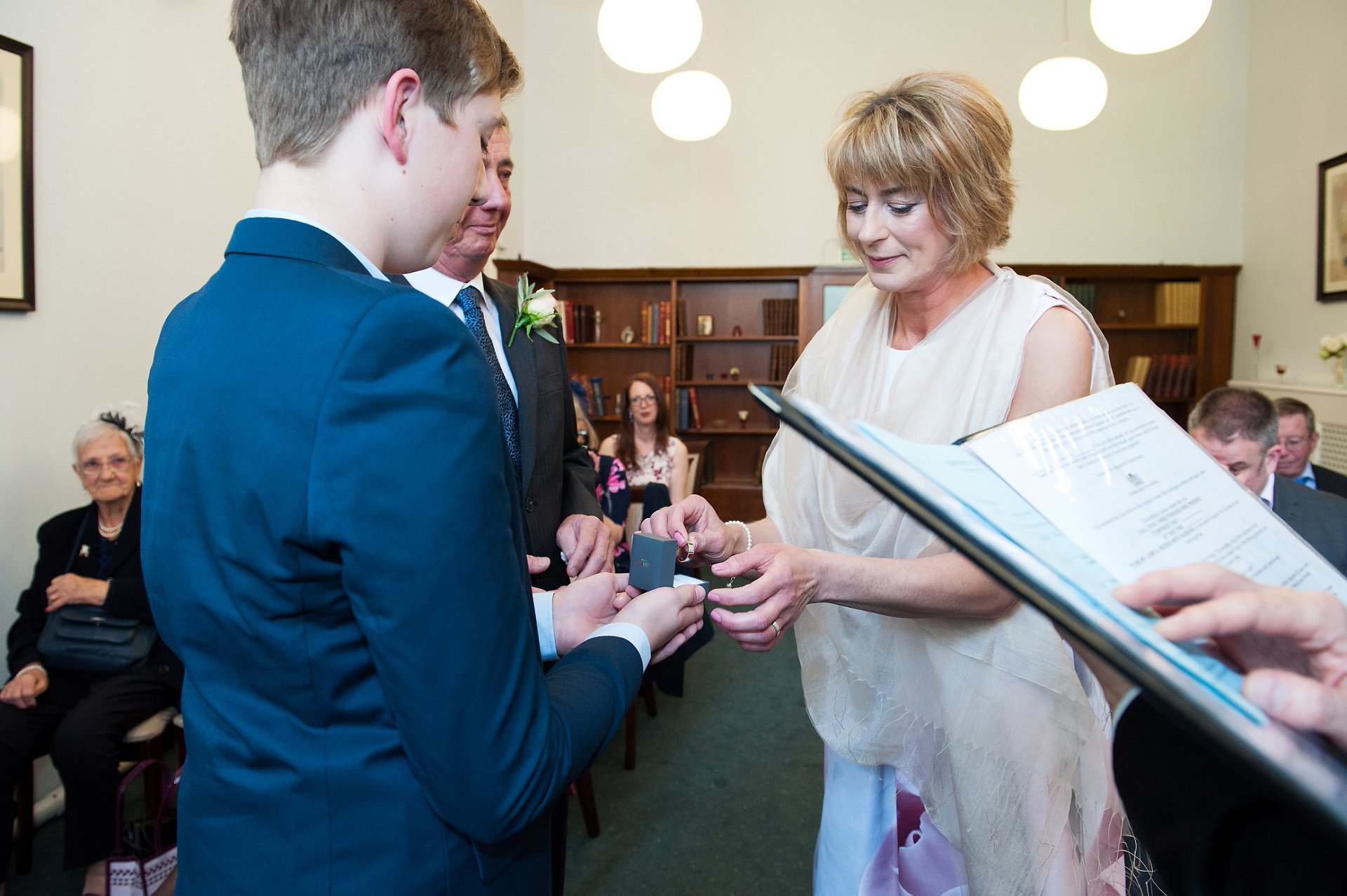 The best man hands over teh rings during this Westminster civil wedding ceremony