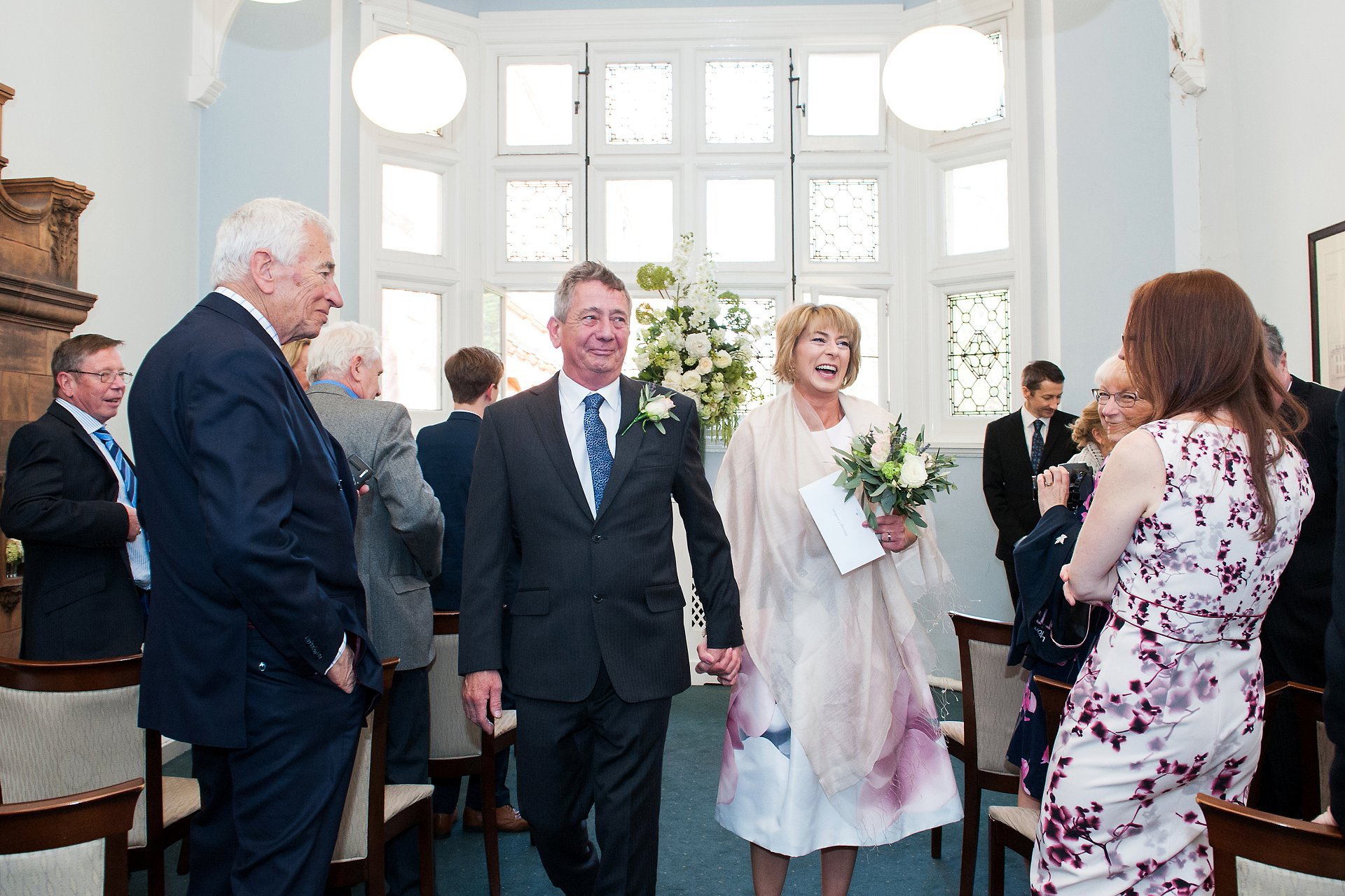 Bride & groom walk back the aisle in the Marylebone Room of Mayfair Library as husband and wife