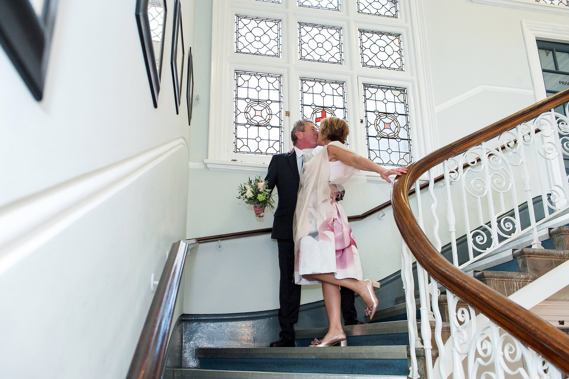A bride & groom kiss on the steps of Mayfair Library, the current Marylebone Register Office
