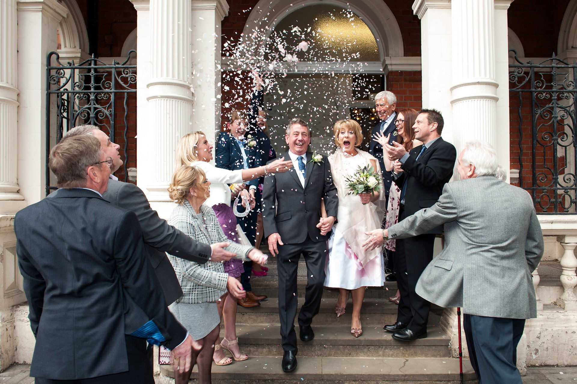 Richoux Wedding Reception and teh Bride & Groom exit Mayfair Library on South Audley Street through a hail of confetti looking so happy to married