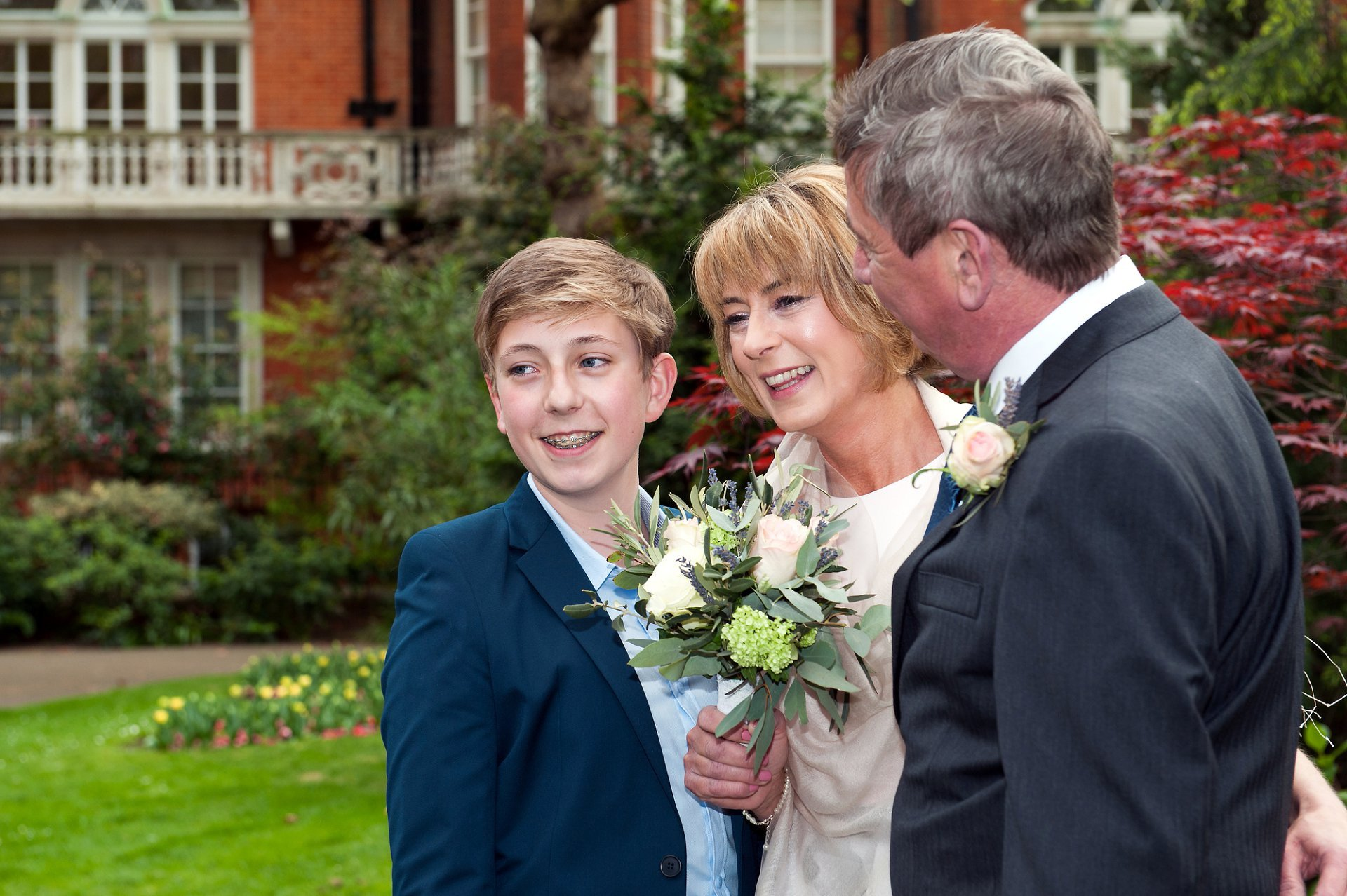 Family pose for wedding photogrpahs in Mount Street Gardens after their civil wedding in next door Mayfair Library