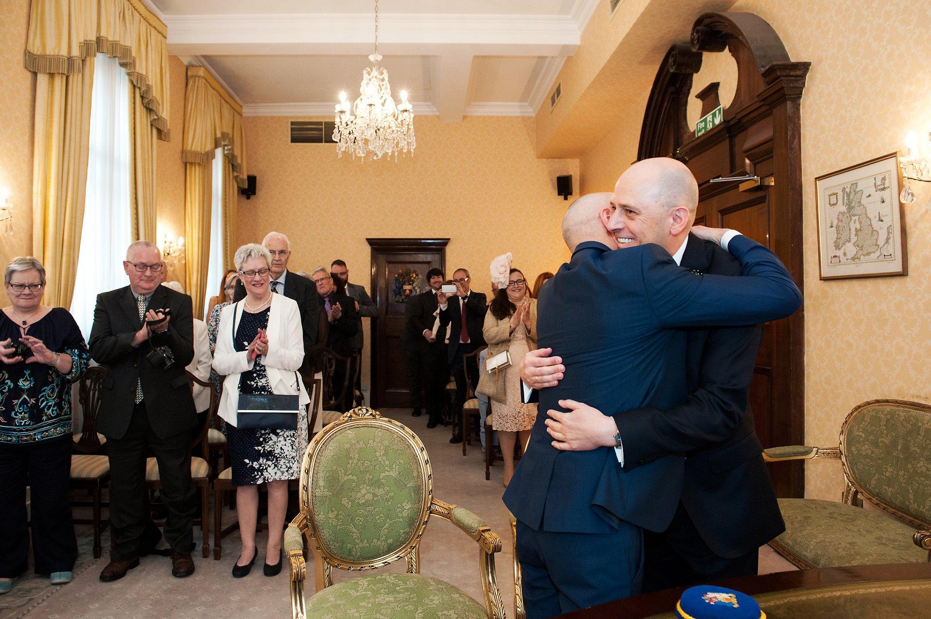 Hugging grooms in Chelsea's Old Town Hall