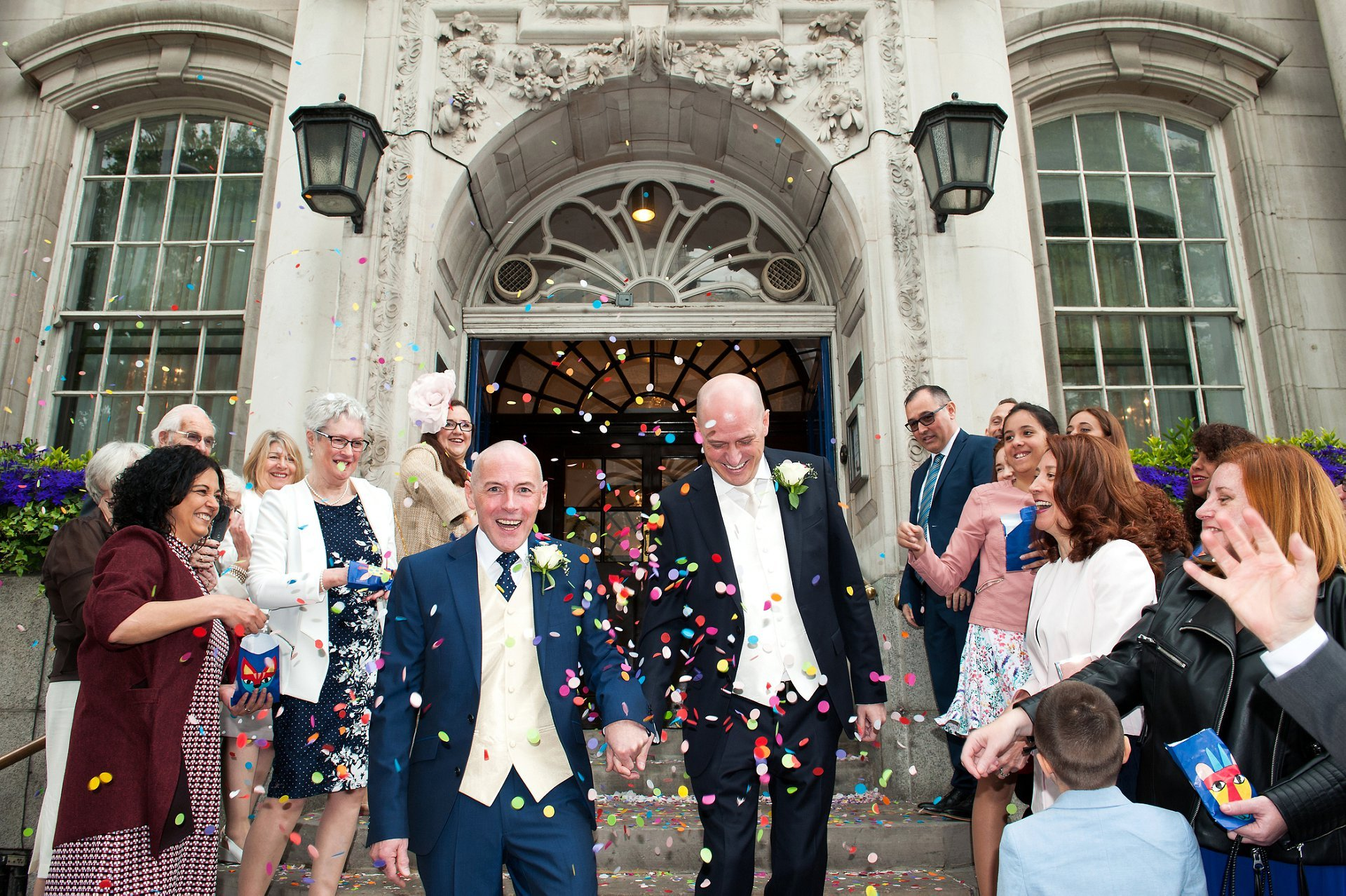 George & Jose on the famous Chelsea Old Town Hall steps with friends and family throwing loads of mulit-coloured confetti