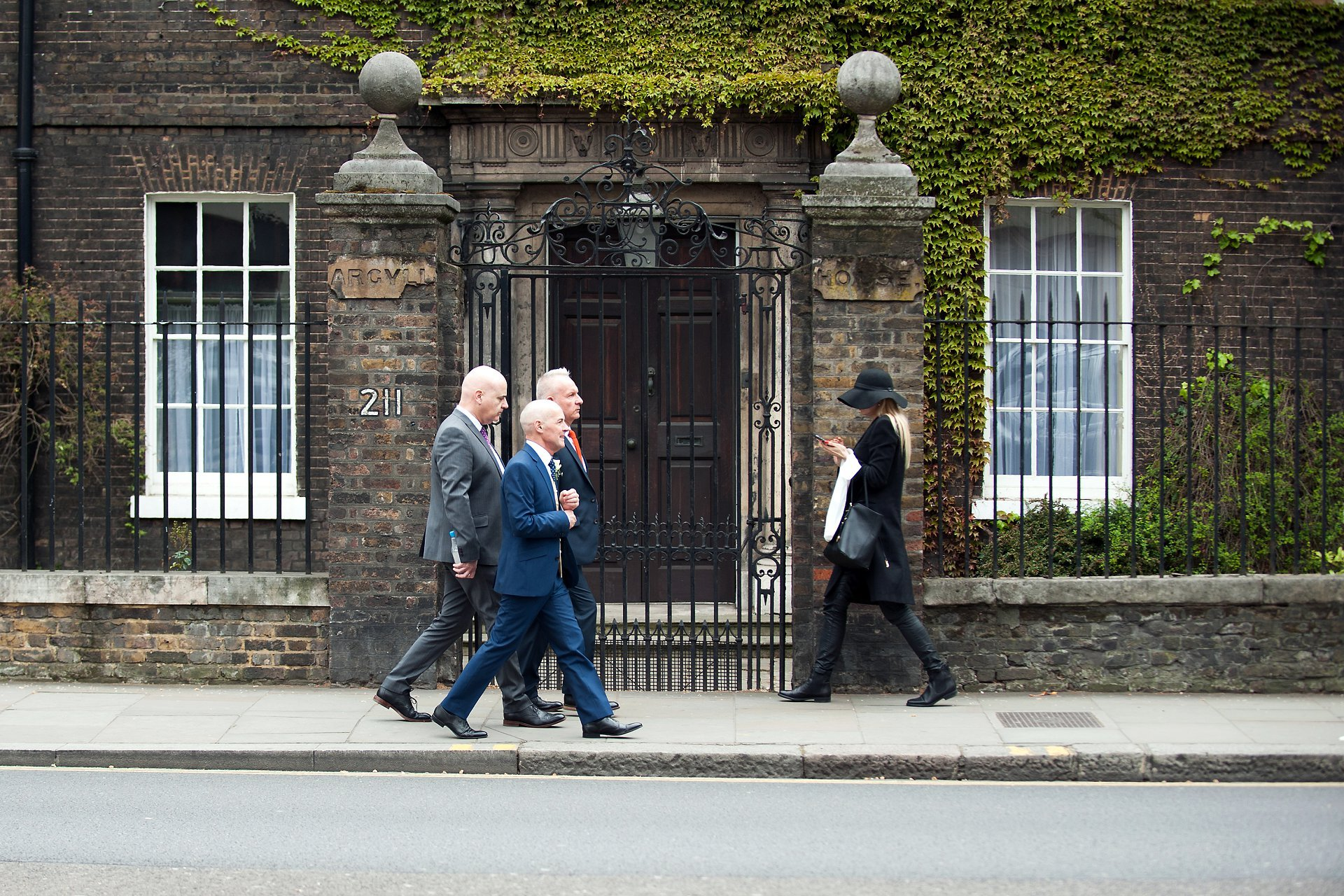 George and friends walking past a typical Chelsea woman on London's King's Road after his wedding