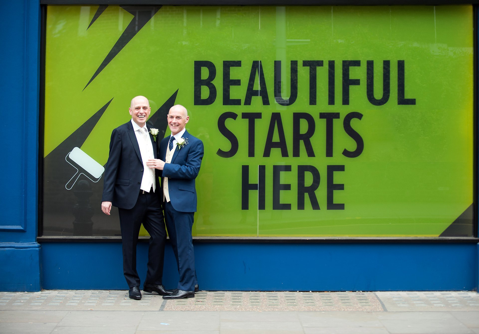"""Jose and George celebrate their marriage on London's King's Road next to a window display """"Beautiful Starts Here"""""""
