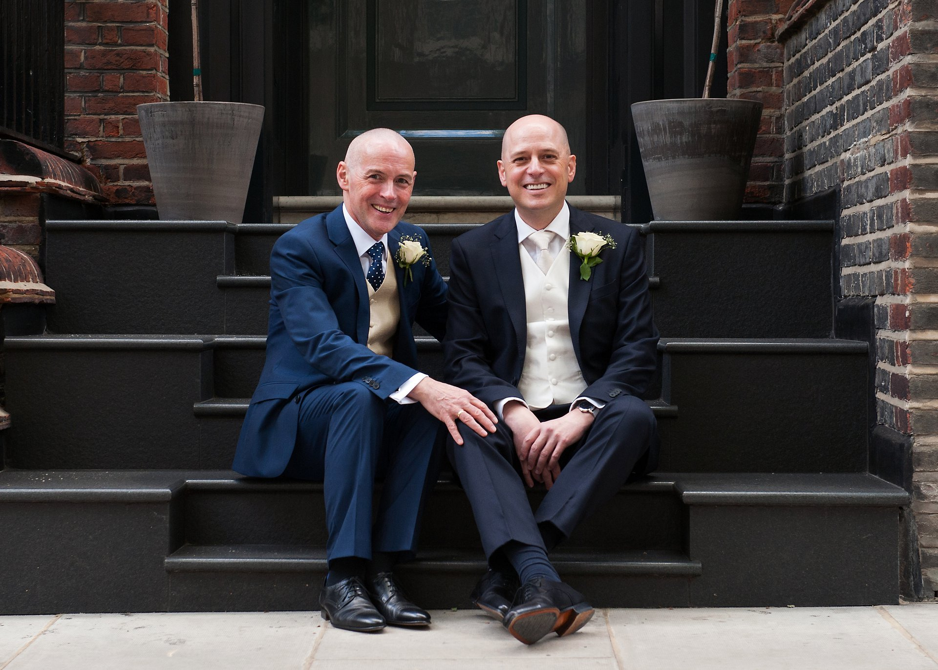 The two grooms relax on a Chelsea step