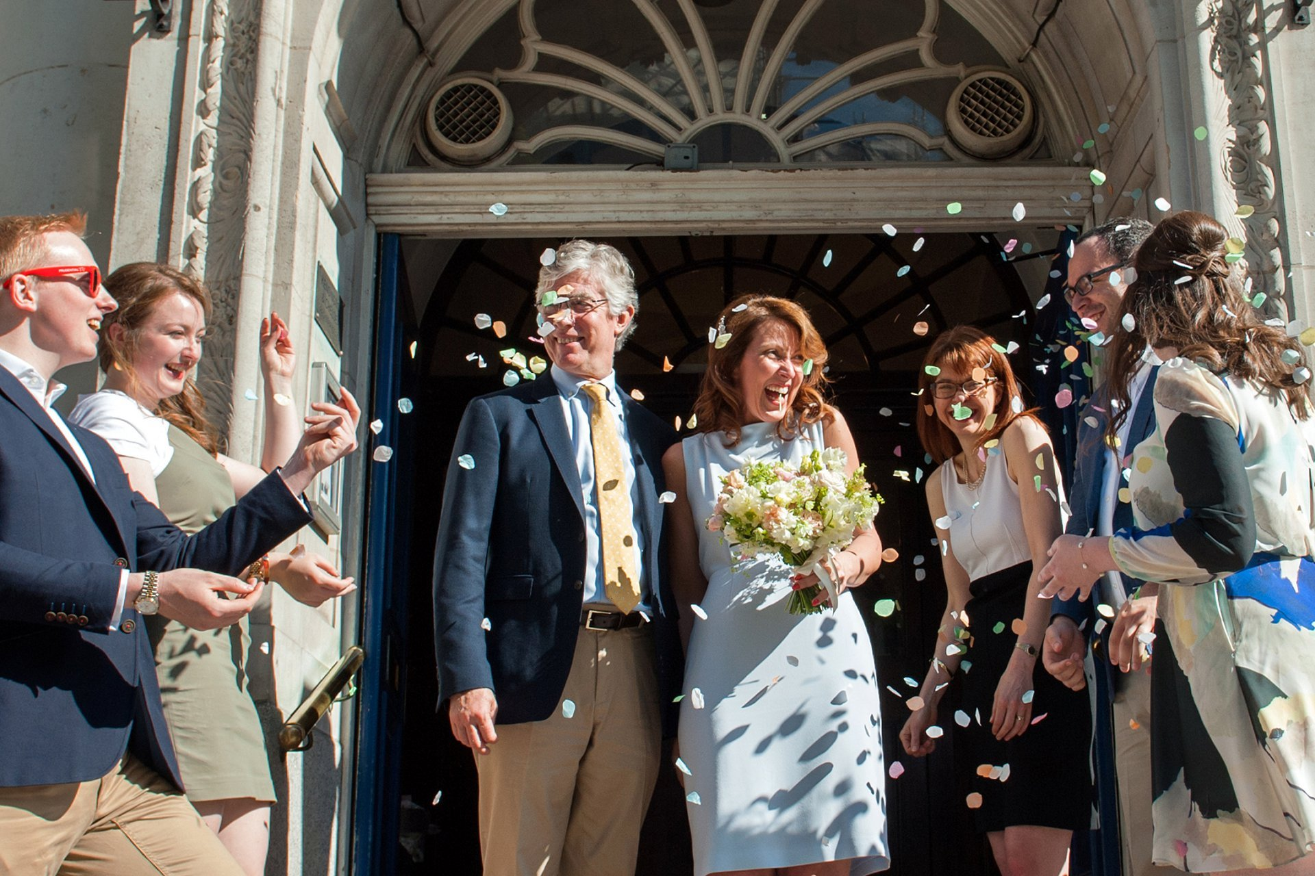 Bride and groom celebrate their Chelsea wedding on the steps of Chelsea Register Office
