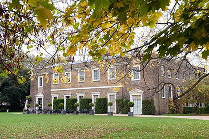 Fulham Palace and the south lawn in Autumn with trees framing the stunning rear aspect of the Grade I listed building