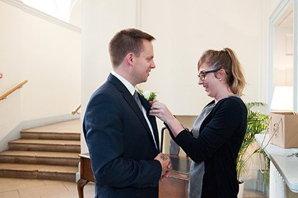 Chloe Goreham from Bovingdons Catering at Fulham Palace puts the grrom's buttonhole flower in place just before his civil wedding ceremony