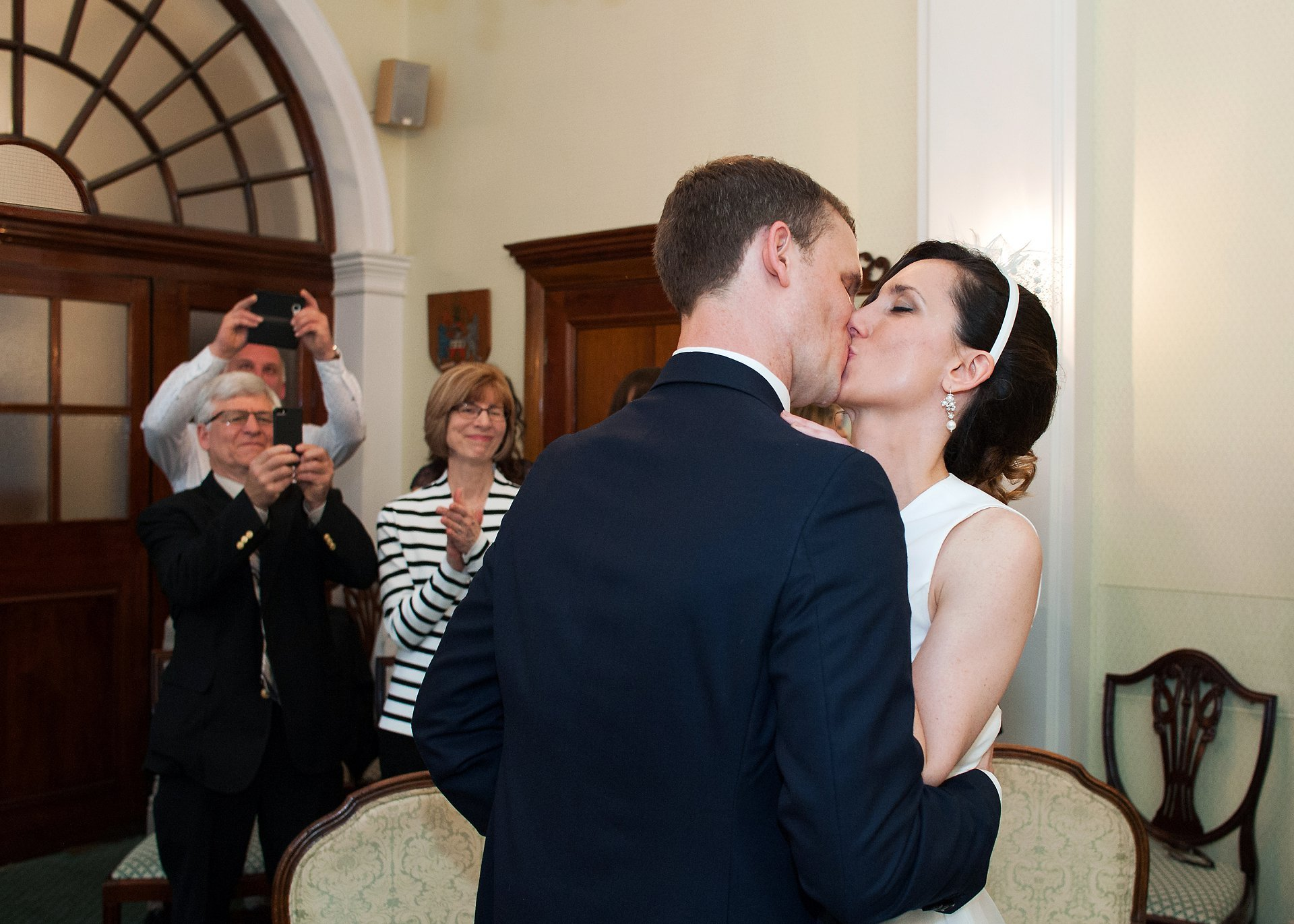 Guests take a photo of a bide and groom kissing to celebrate their Rossetti Room marriage