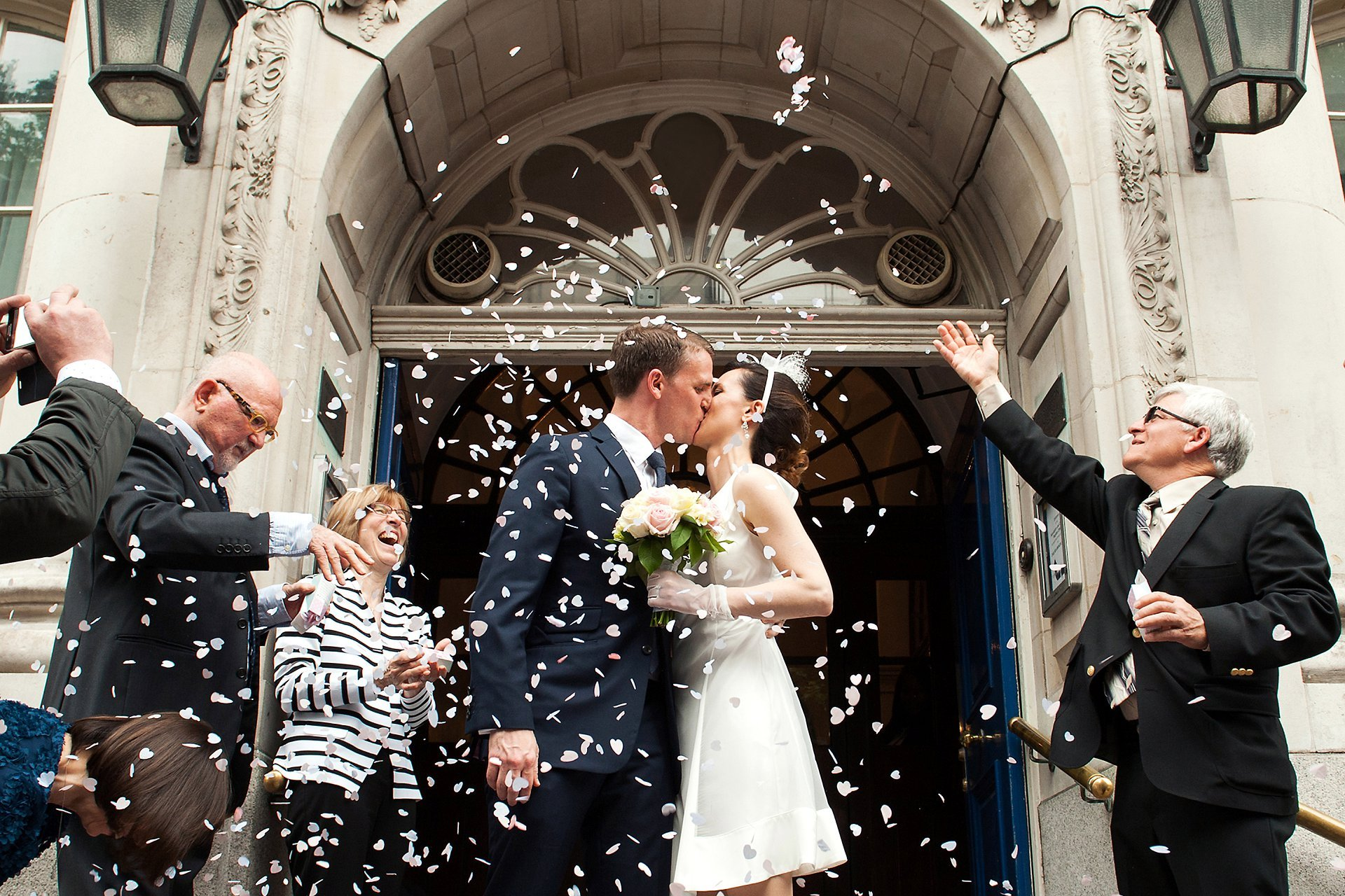 Rossetti Room wedding photographer Emma Duggan for small ceremonies in Chelsea Register Office here showing a bride and groom on the famous steps of Chelsea Old Town Hall with guests throwing confetti