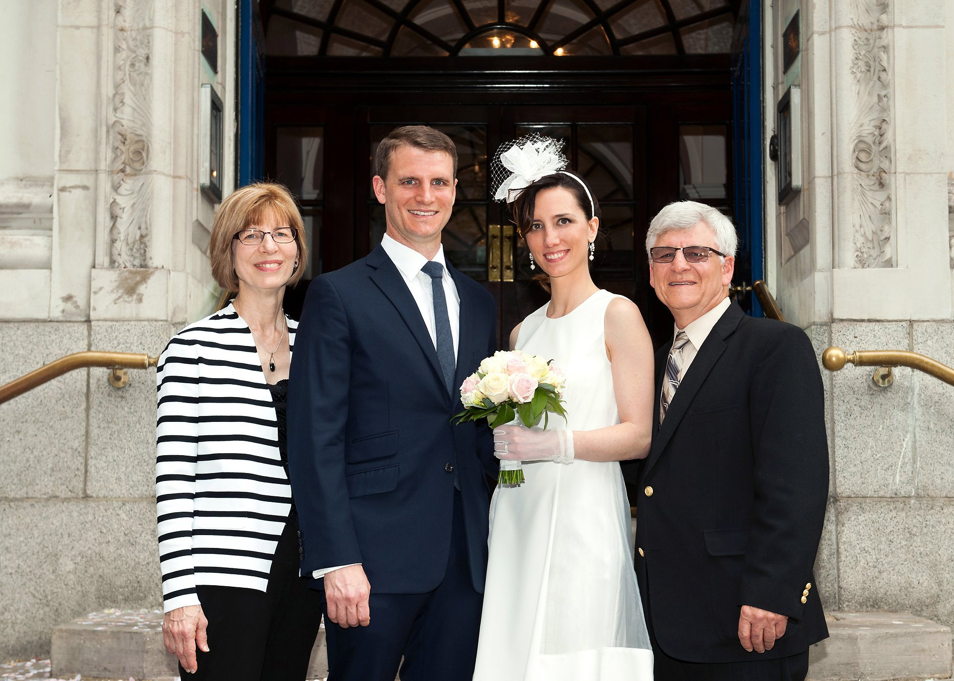 Bride and groom with the groom's parents on the steps outside Chelsea Register Office
