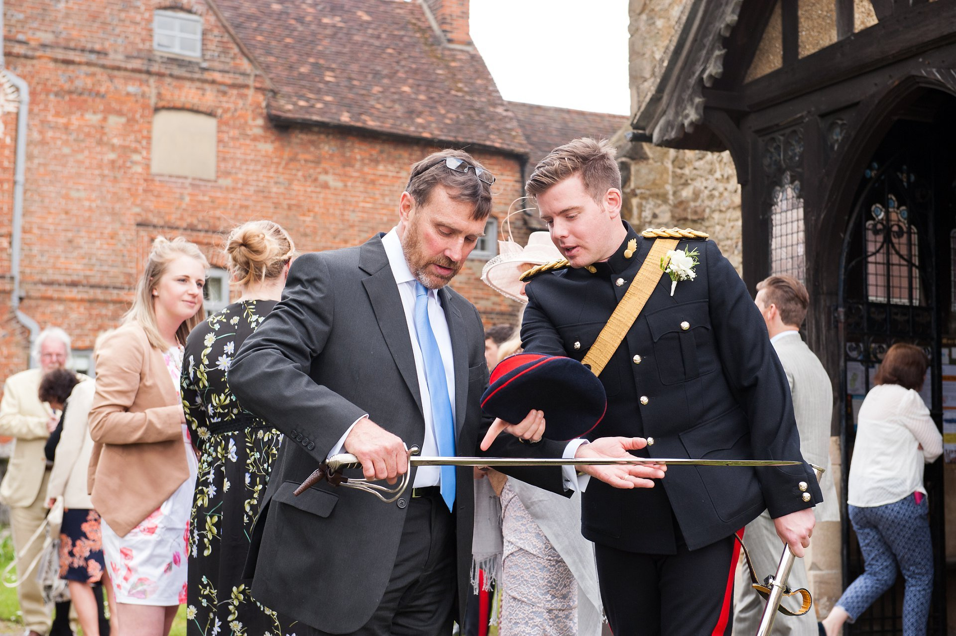 guest looks at groom, sam's, sword outside st mary's church, westerham