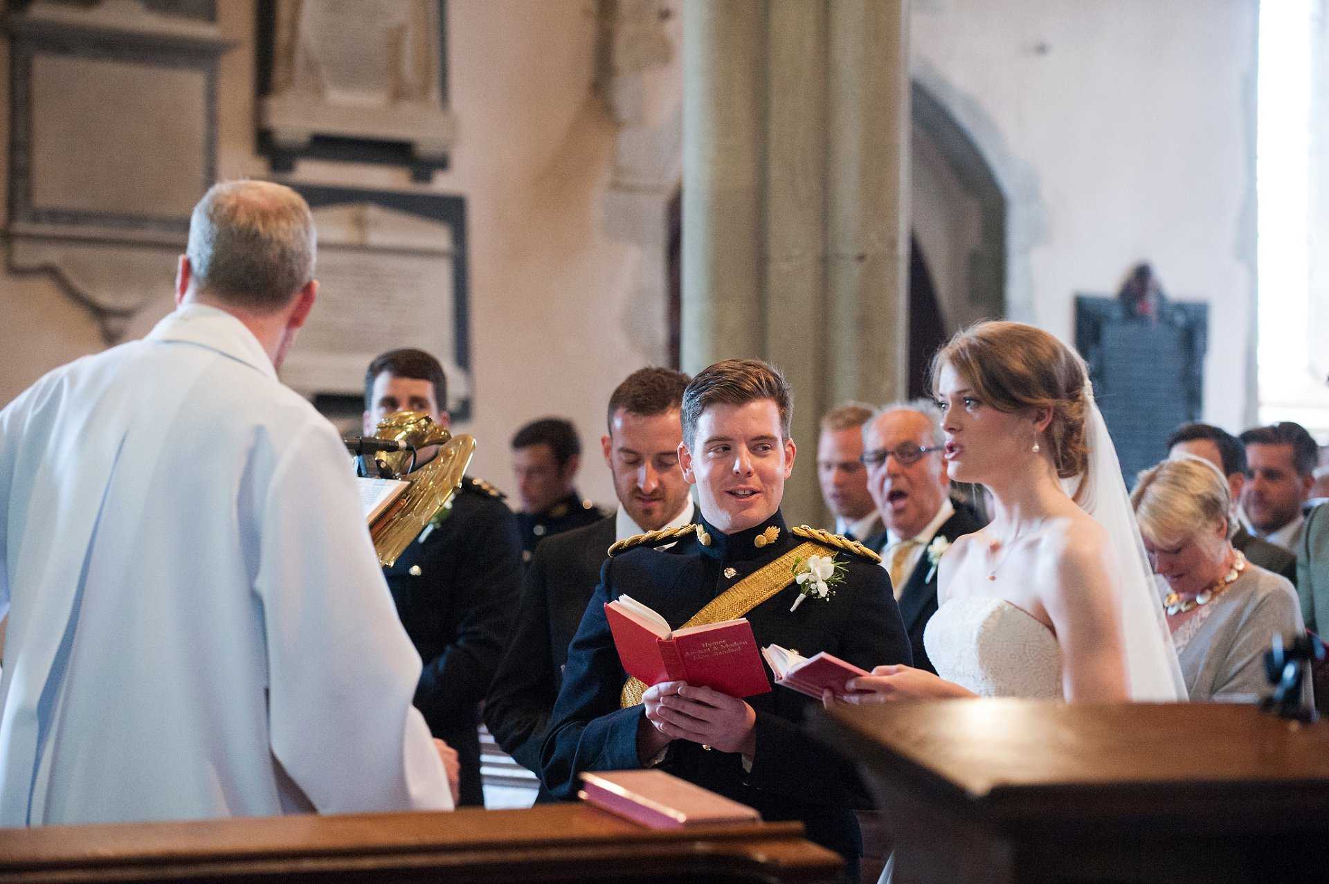 Groom takes a look at his bride during a hymn in St Mary's Westerham